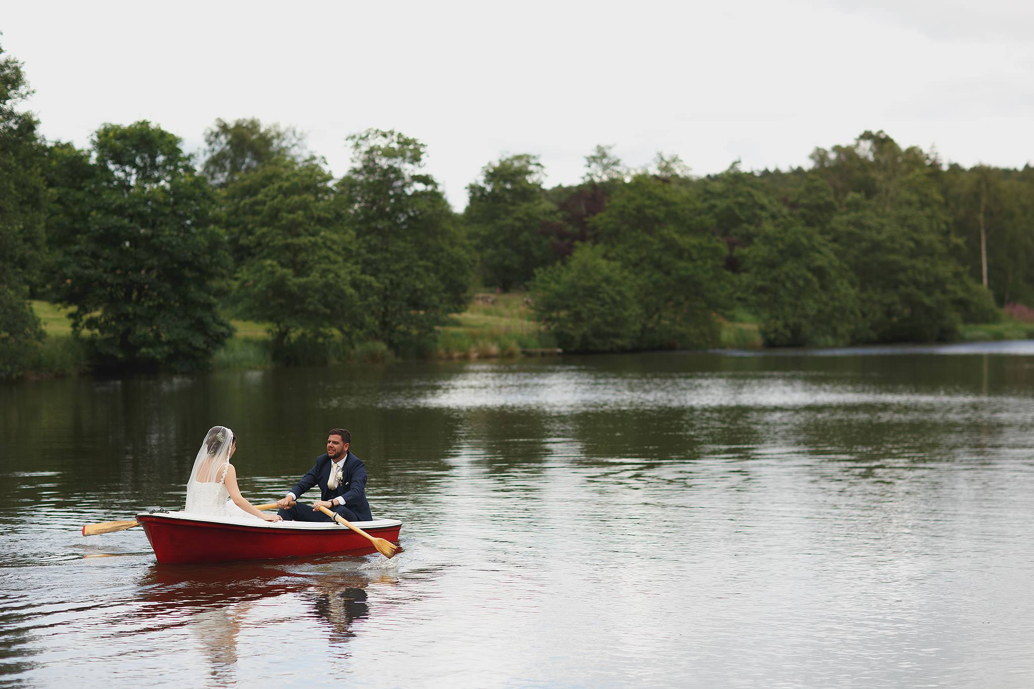 Bride and groom in the rowing boat at Browsholme Hall Wedding.