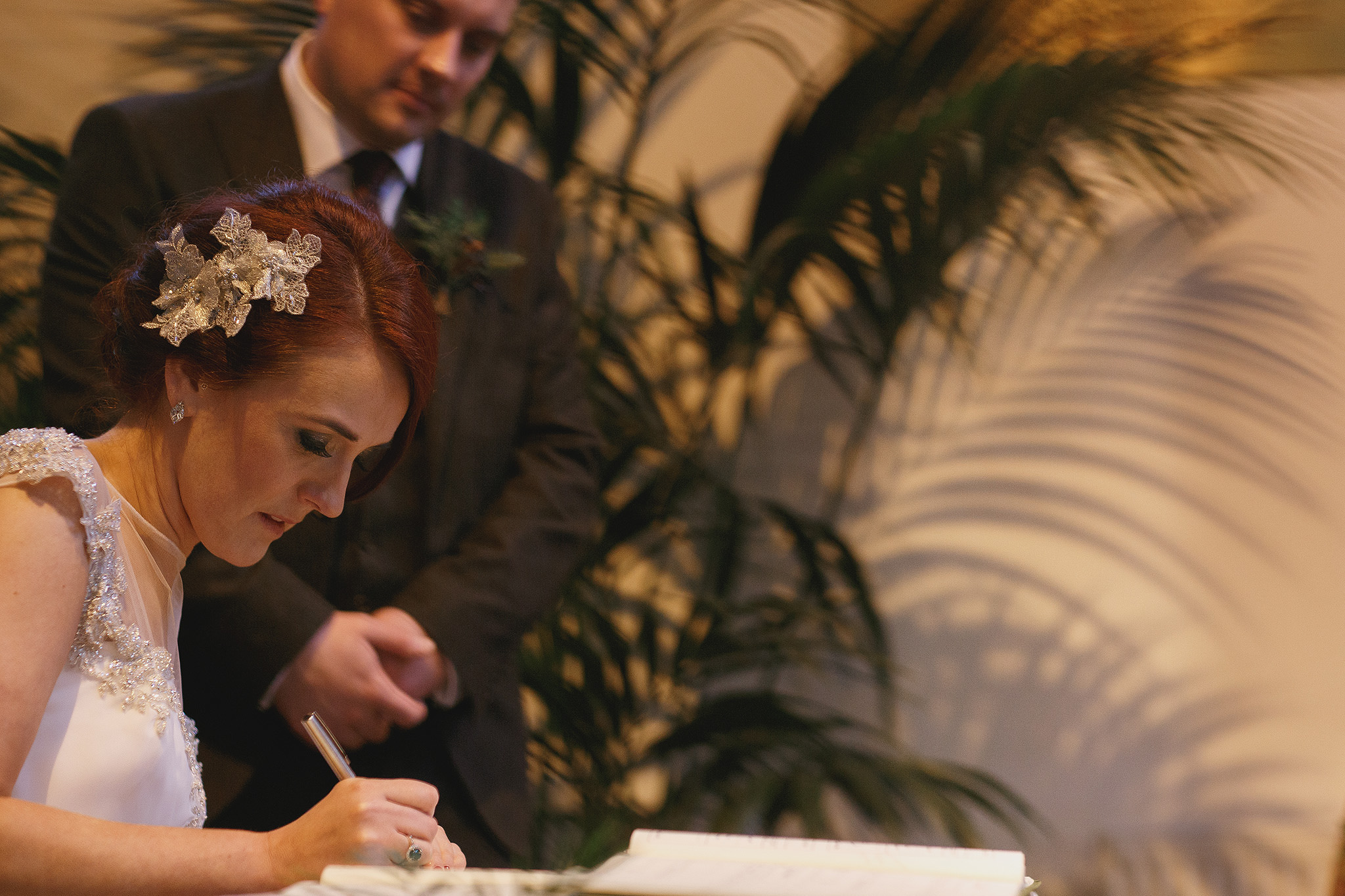 Bride and groom signing the register in St Mary's Church Lancashire.