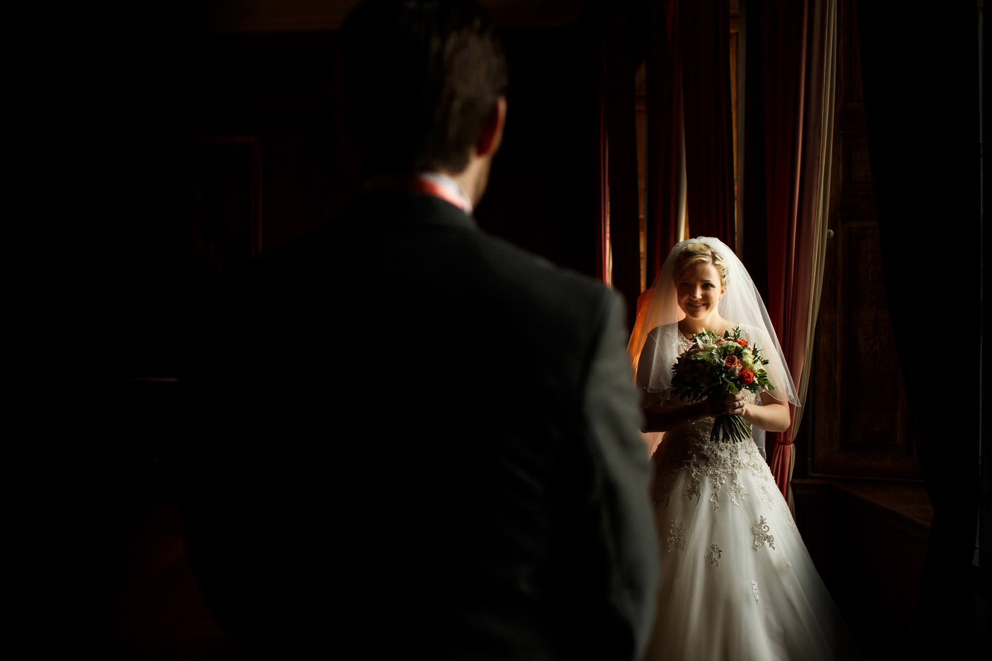 Bride and Groom facing one another in the window light at Adlington Hall and Gardens