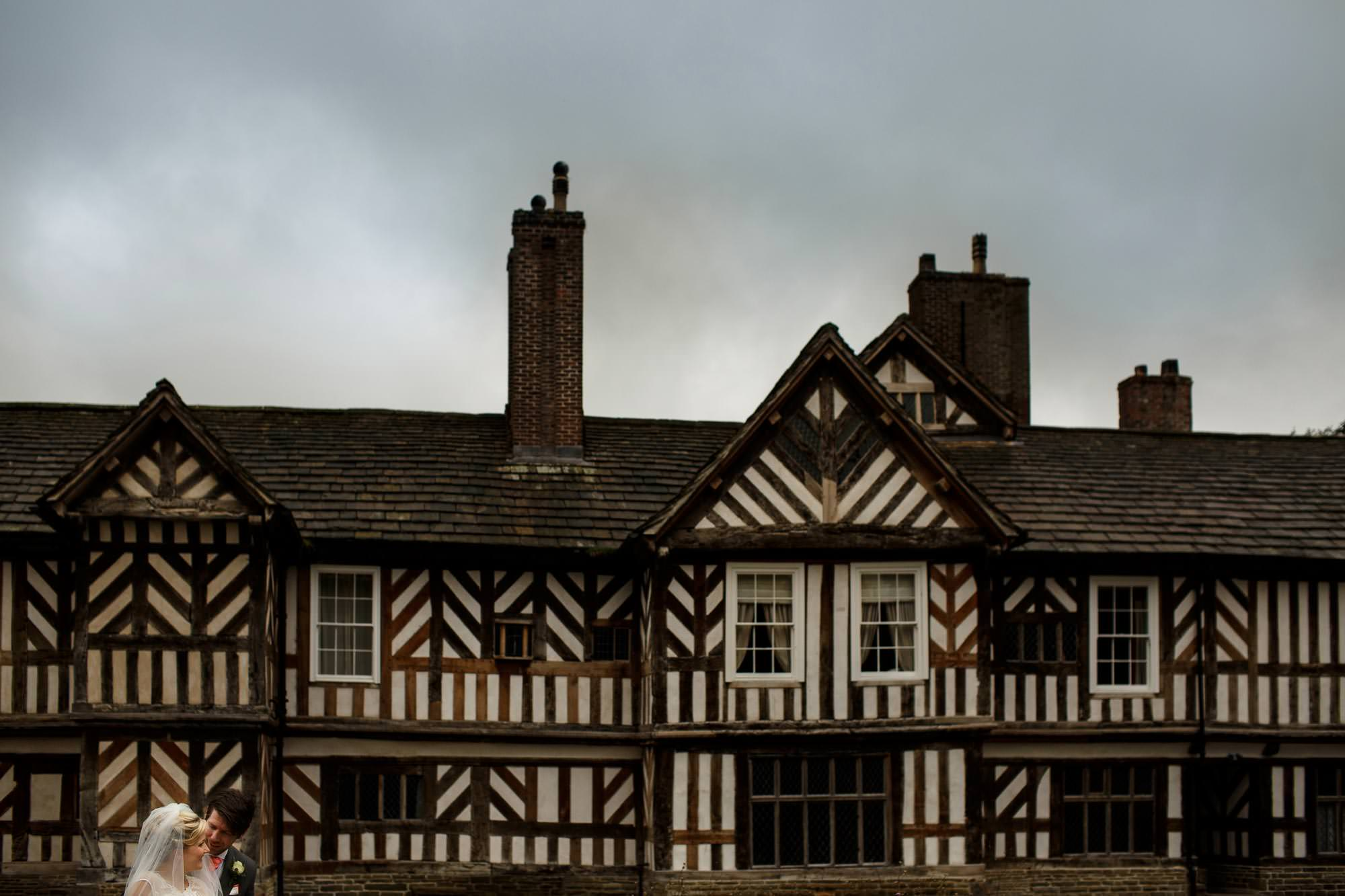 Bride and Groom Outside the front of Adlington Hall and Gardens showing off the tudor exterior