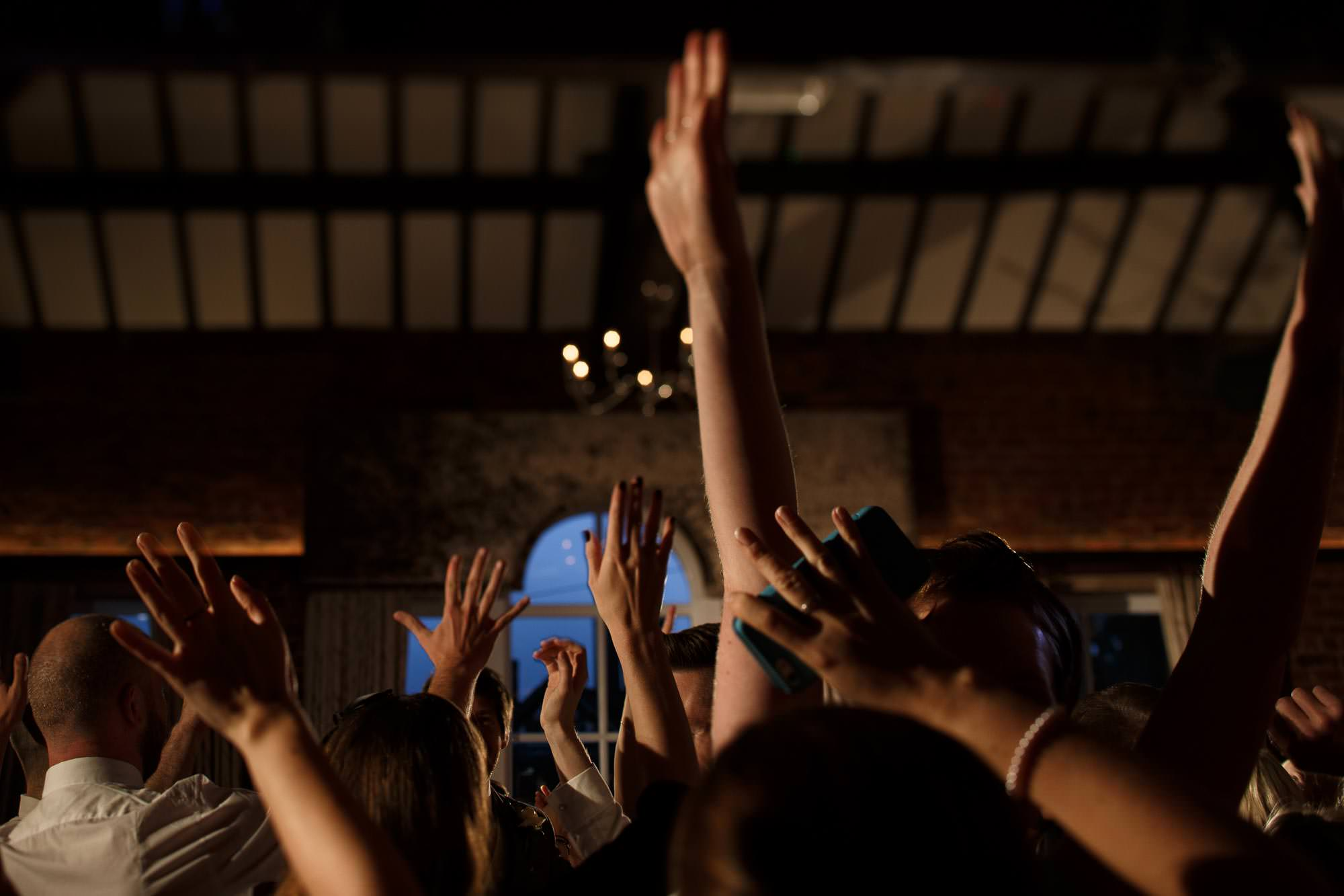 Guests waving their arms in the air whilst dancing at Adlington Hall and Gardens