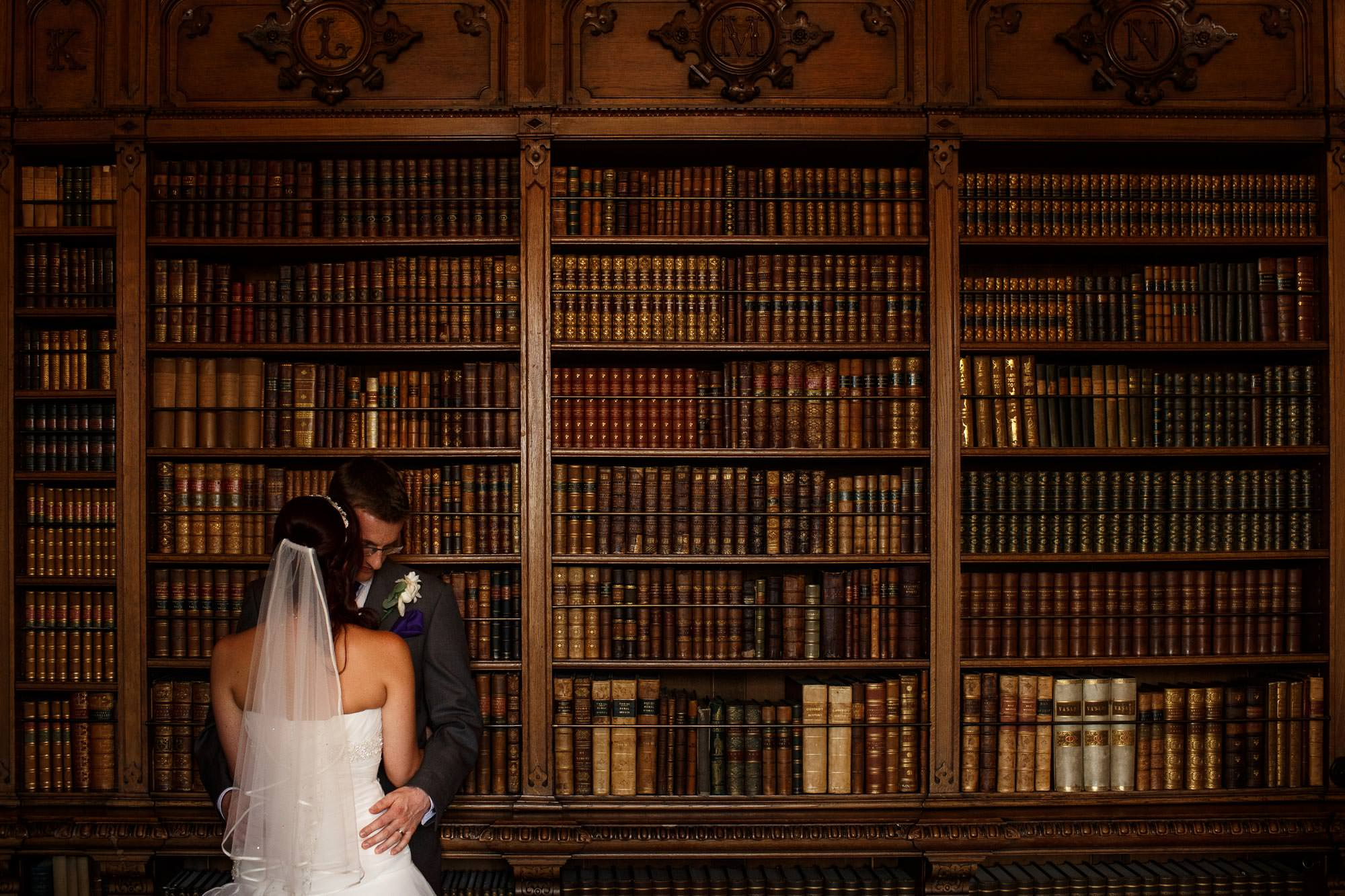 Bride and groom hugging in the library at Arley Hall