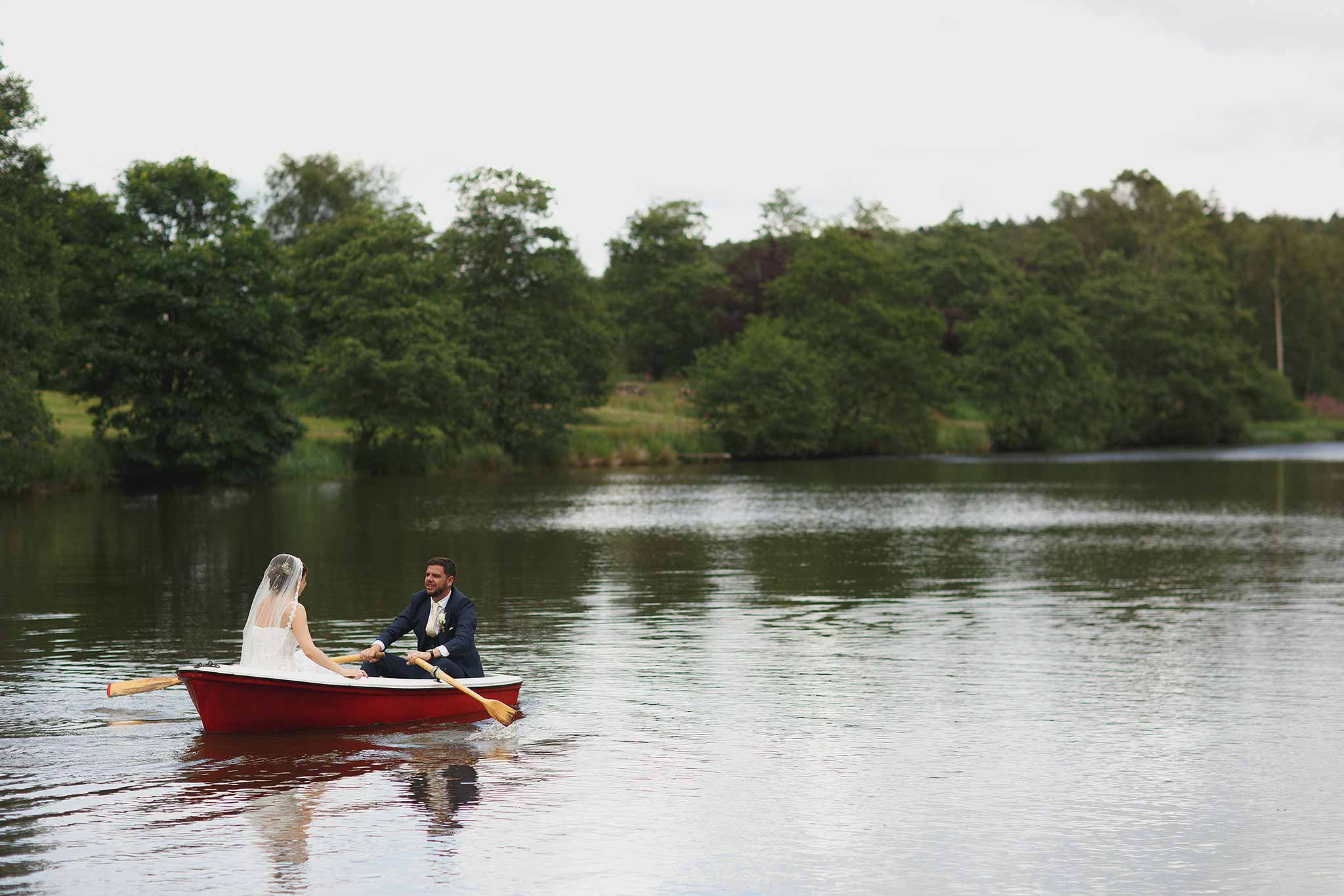 Bride and Groom in a rowing boat on the lake at browsholme hall