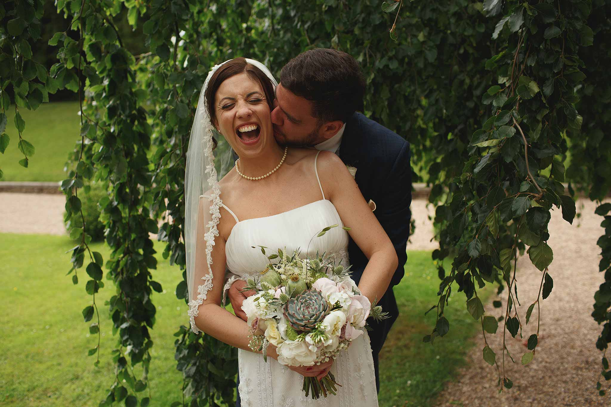 Bride and Groom laughing in the willow tree at Browsholme Hall
