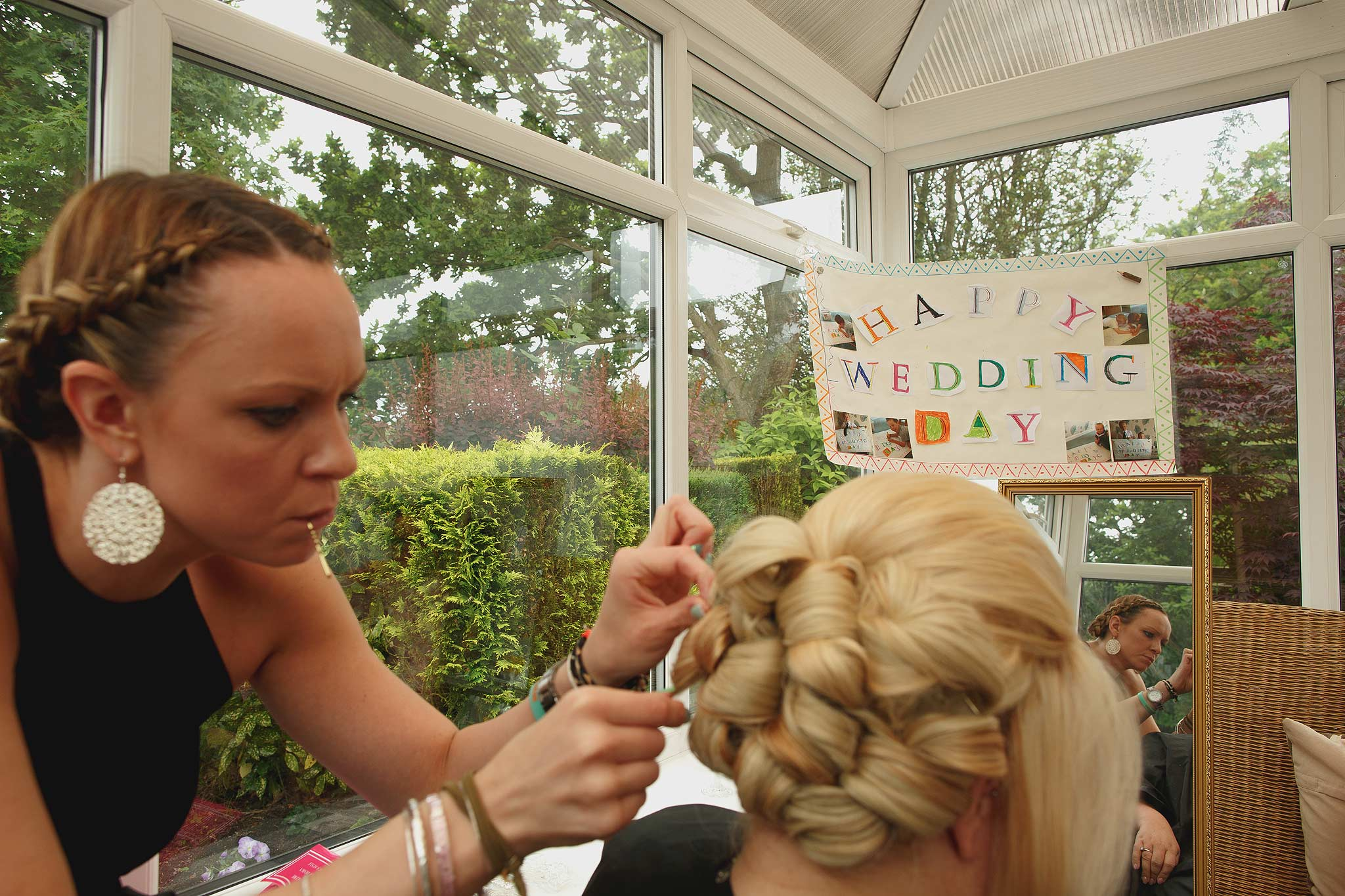 Bride having hair touched up by hairdresser