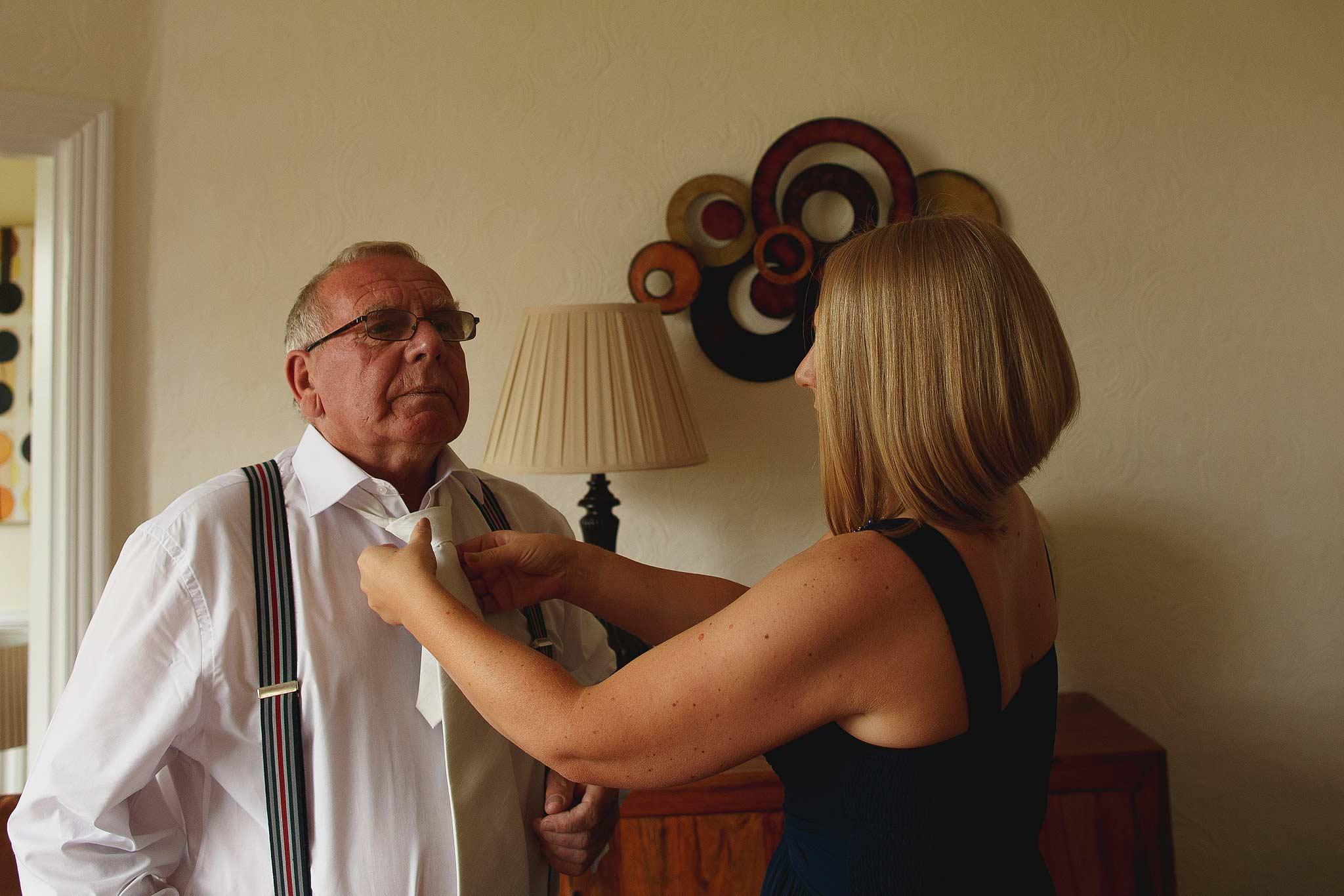 Daughter helping his dad with his tie on the morning of the wedding