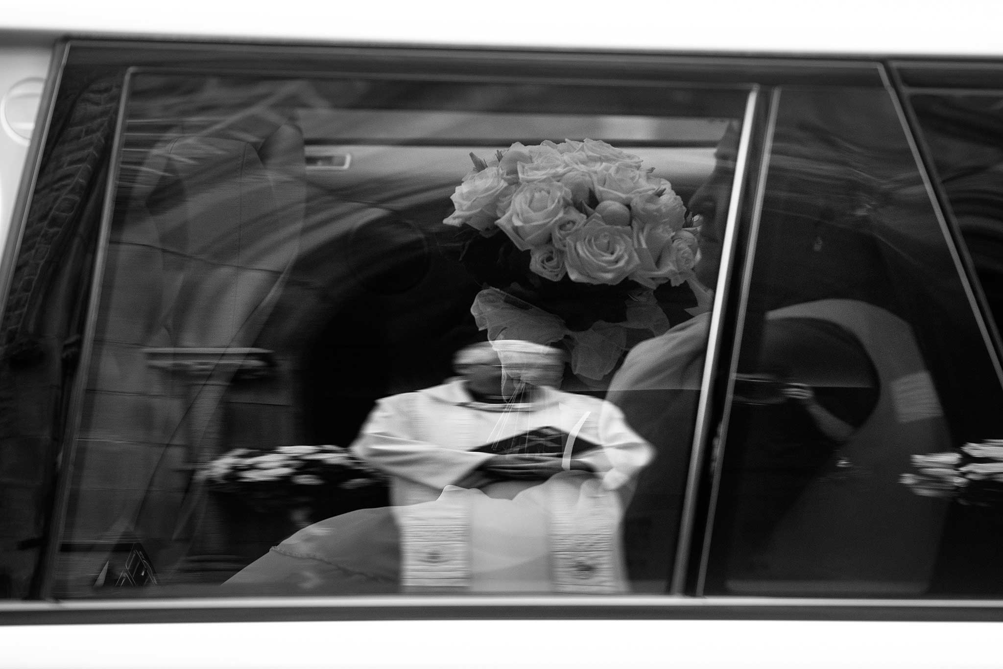 Reflection in the car window of the priest and bride