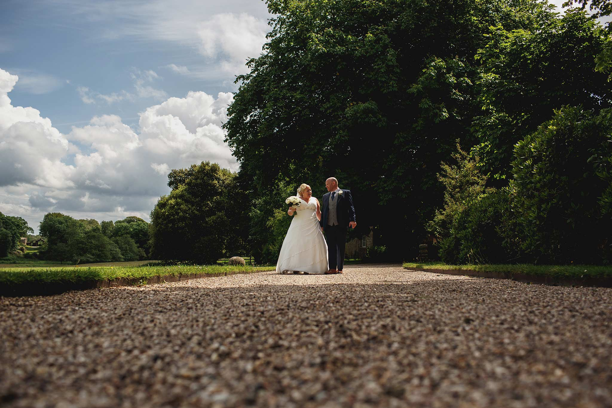 Bride and groom walking outside Browsholme Hall