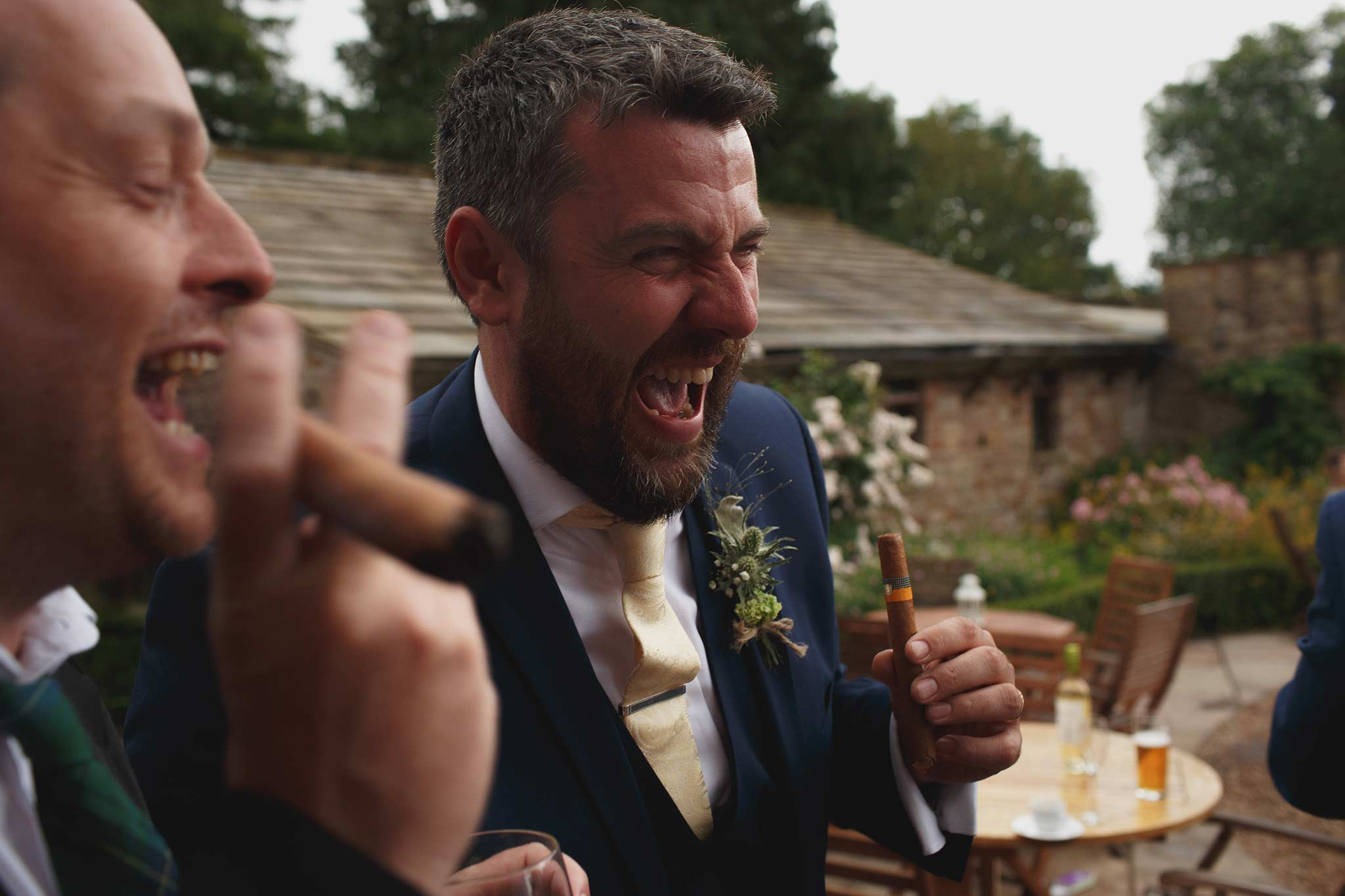 groomsmen smoking cigar at a wedding