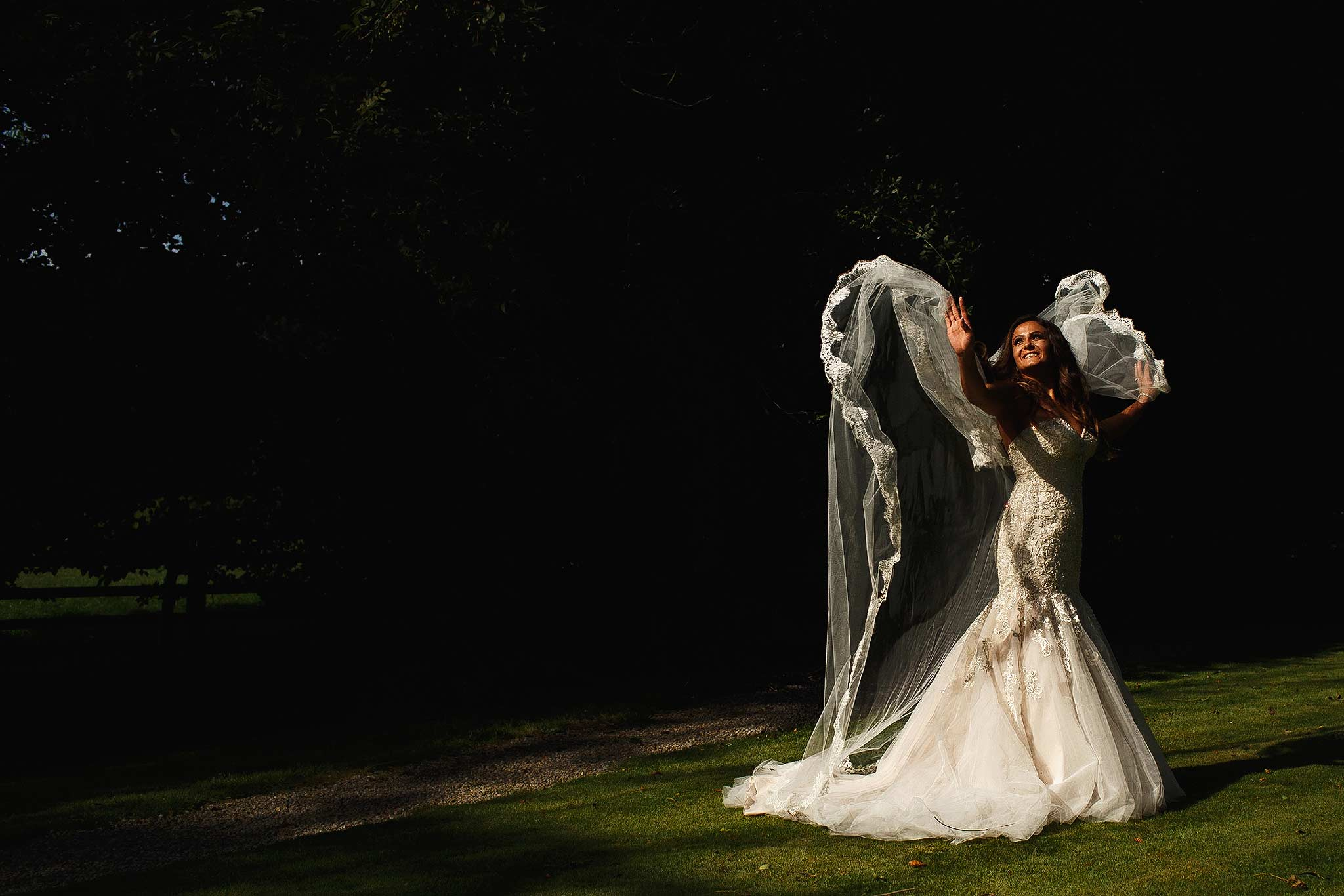 Brides veil flowing in the air like an angel in the gardens at mitton hall