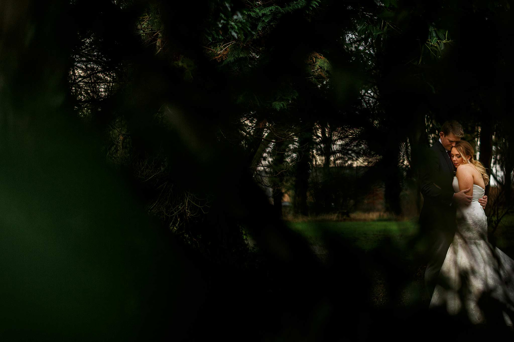 photograph of bride and groom through the trees at mitton hall wedding