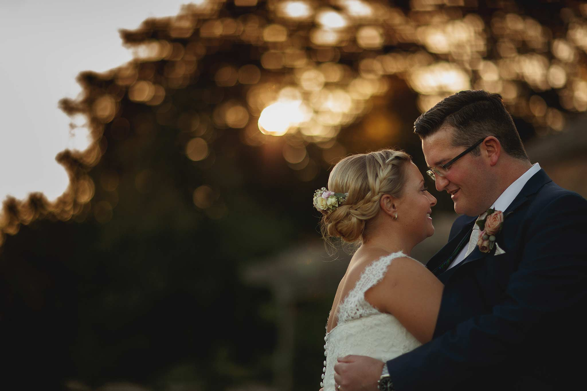 nice bokeh behind bride and groom at sunset