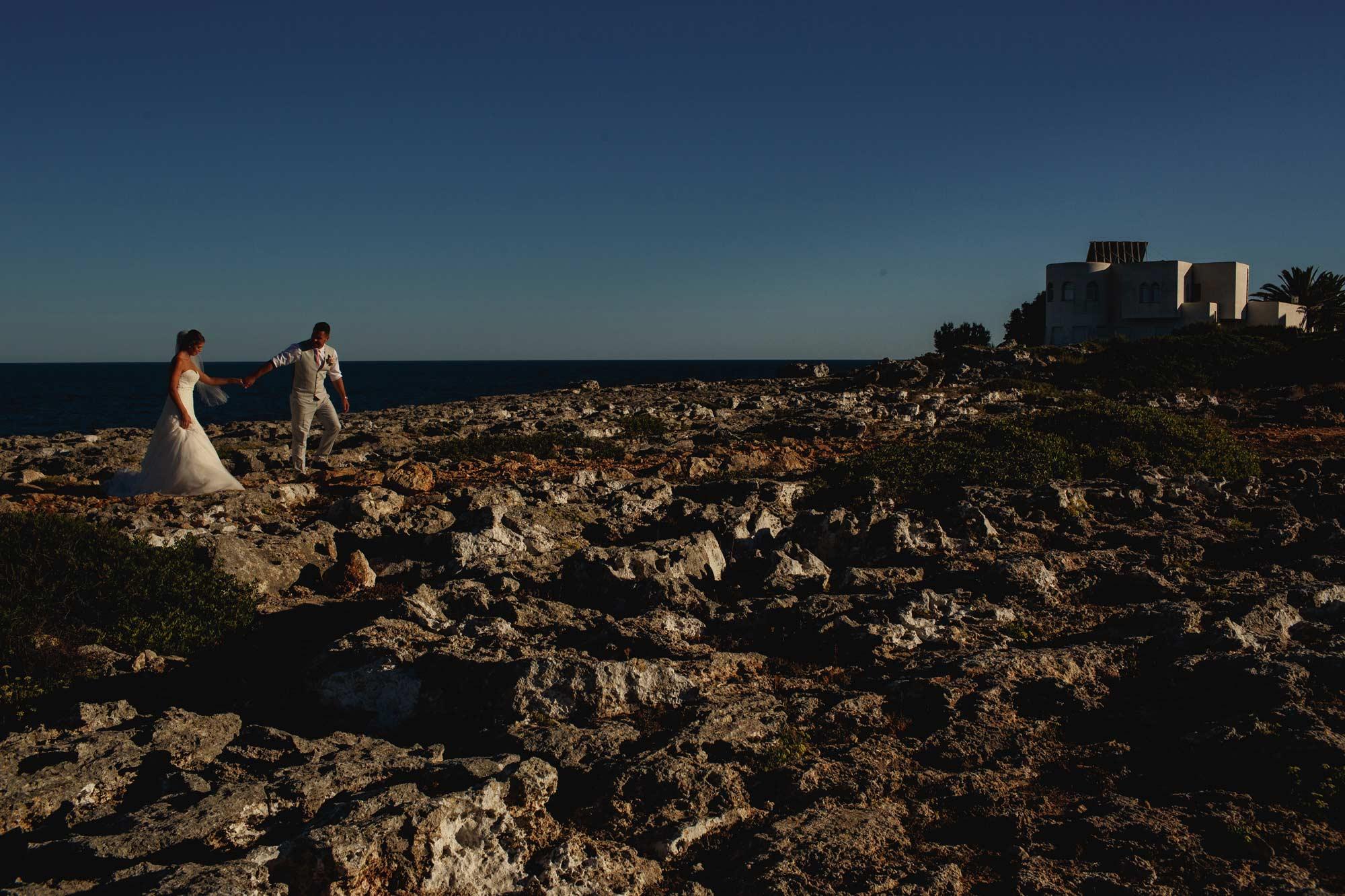 Bride and Groom walking across the rocks in Spain