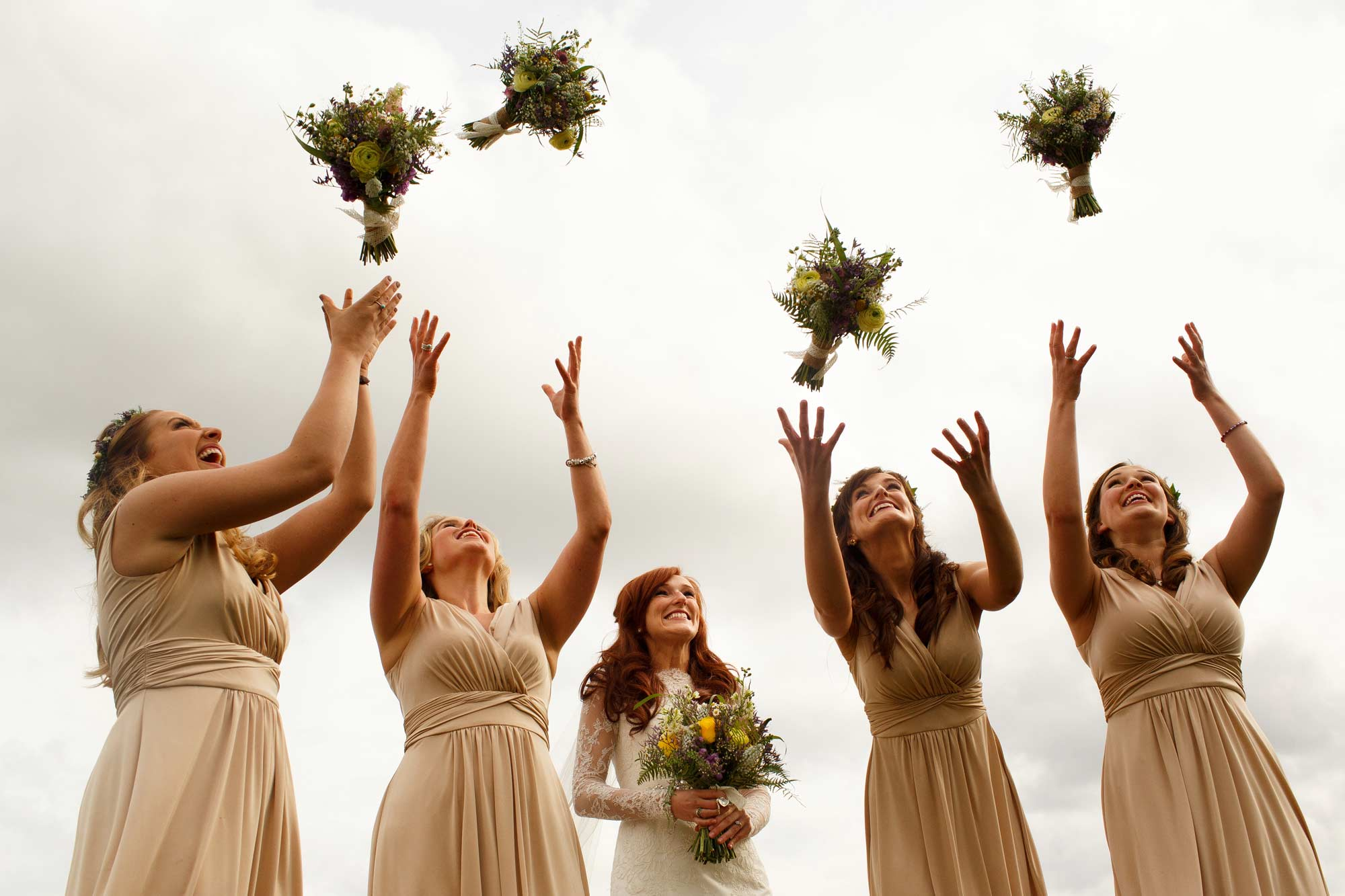 Bridesmaids all throwing the bouquets in the air at Sandhole Oak Barn