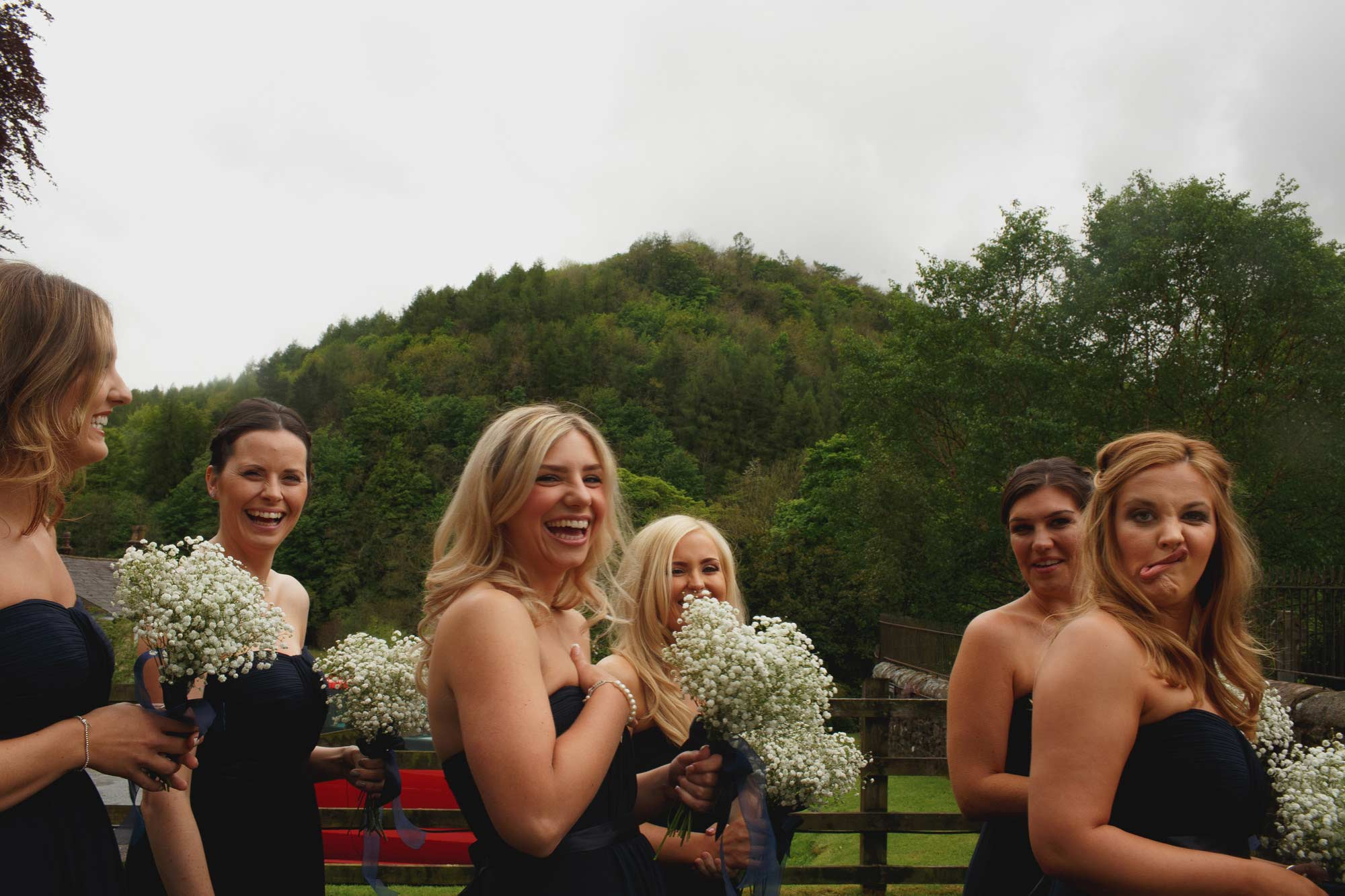 Bridesmaids waiting to go in the church outside inn at whitewell