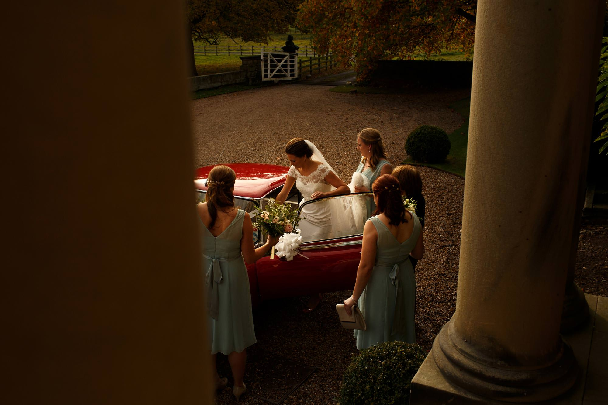 Bride and bridesmaids getting into red sports car at Iscoyd Park wedding