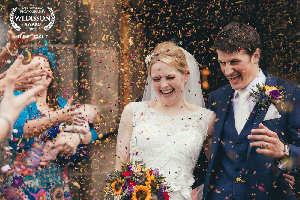 Bride and groom entering a confetti storm as they exit church