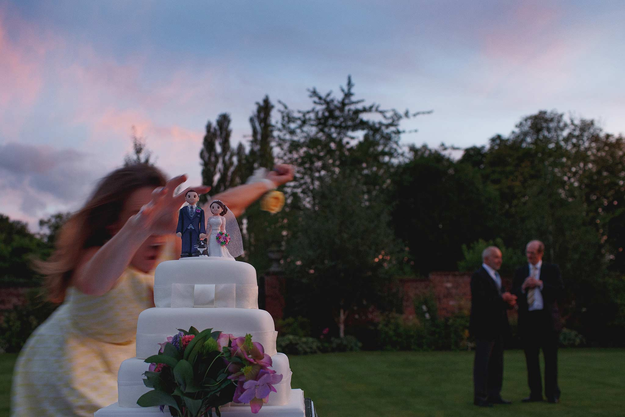 Award winning wedding photograph of someone almost knocking over a wedding cake at Colshaw Hall