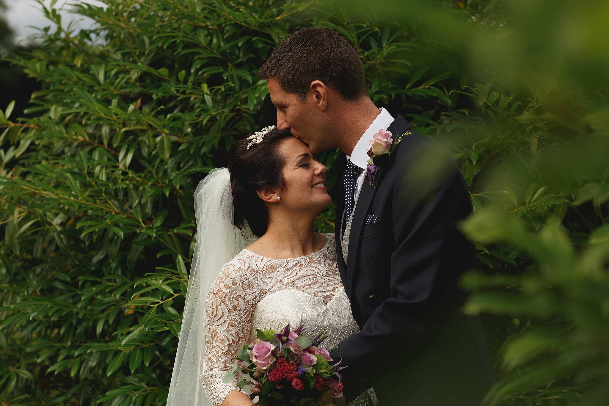Groom kissing bride on the head in the gardens at colshaw hall