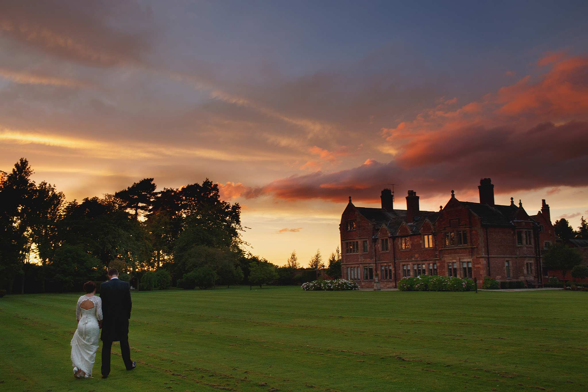 wide angle image of a bride and groom walking away at sunset at colshaw hall