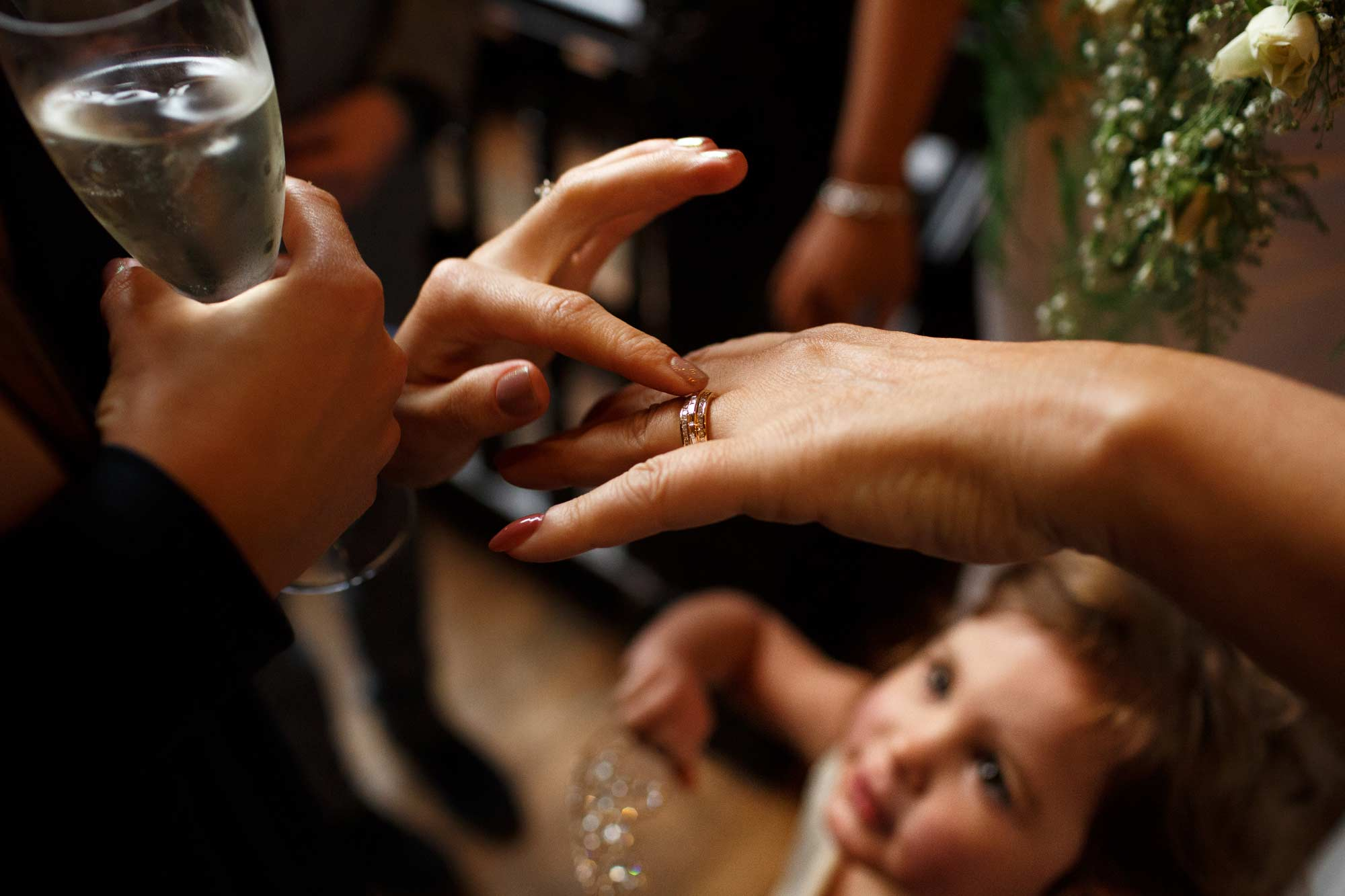 Documentary wedding photograph of bride showing guests her new ring with a girl looking up