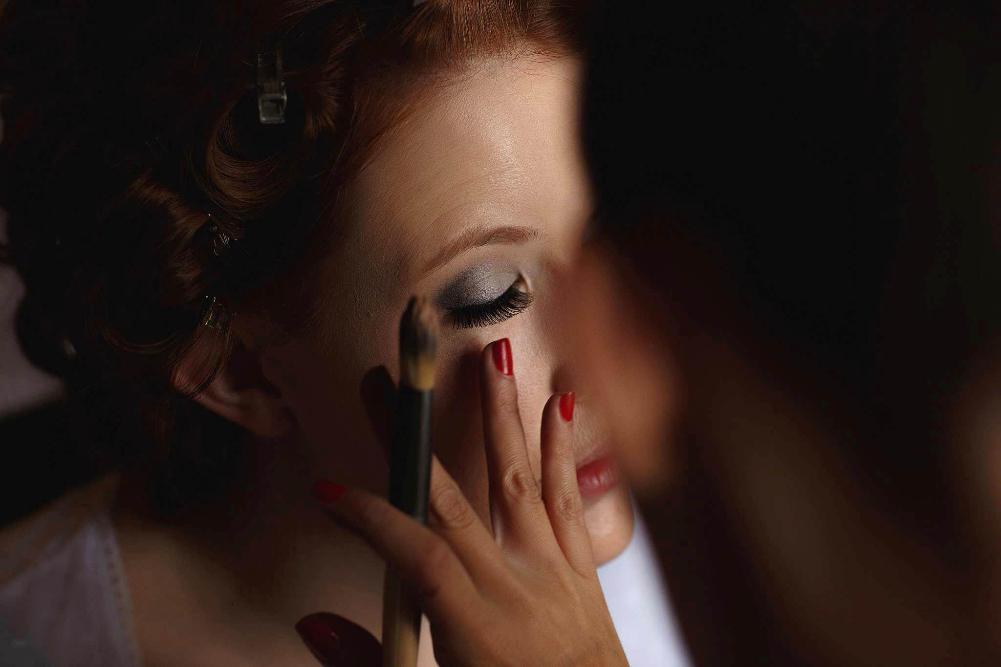 bride having make-up applied at wedding