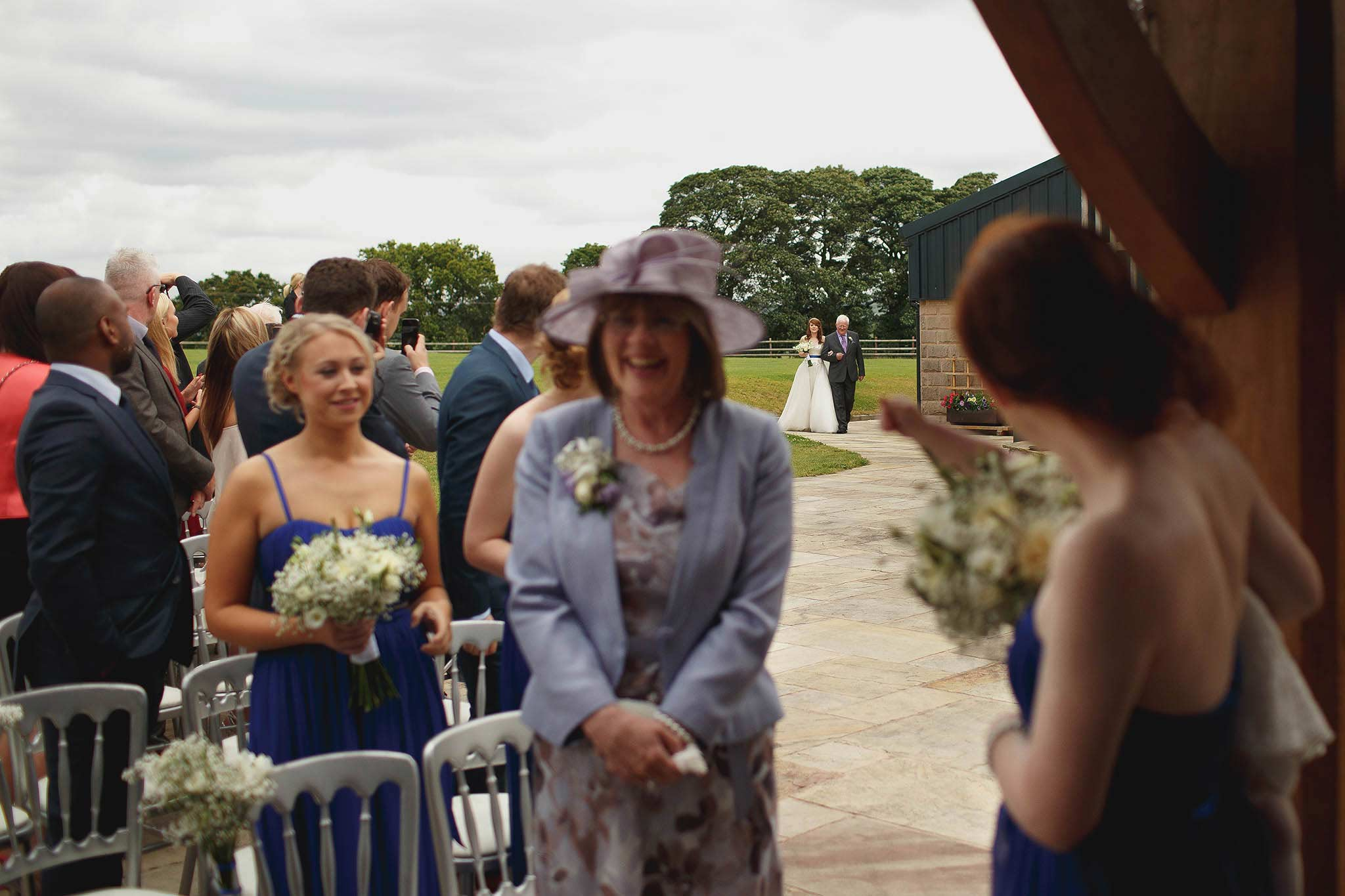 bride walking down the aisle at outdoor wedding ceremony at Heaton House Farm