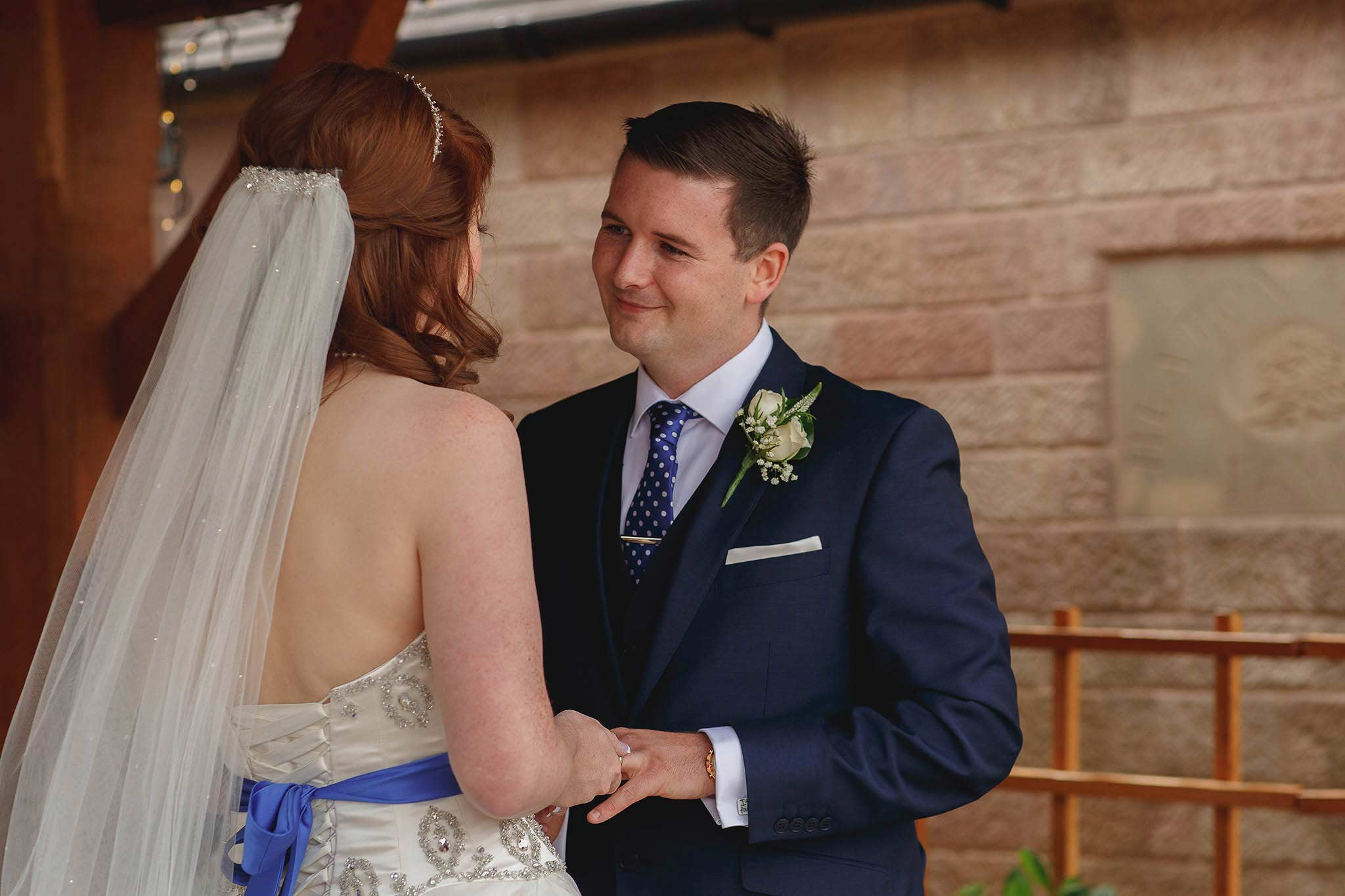 groom looking at bride during wedding ceremony at Heaton House Farm