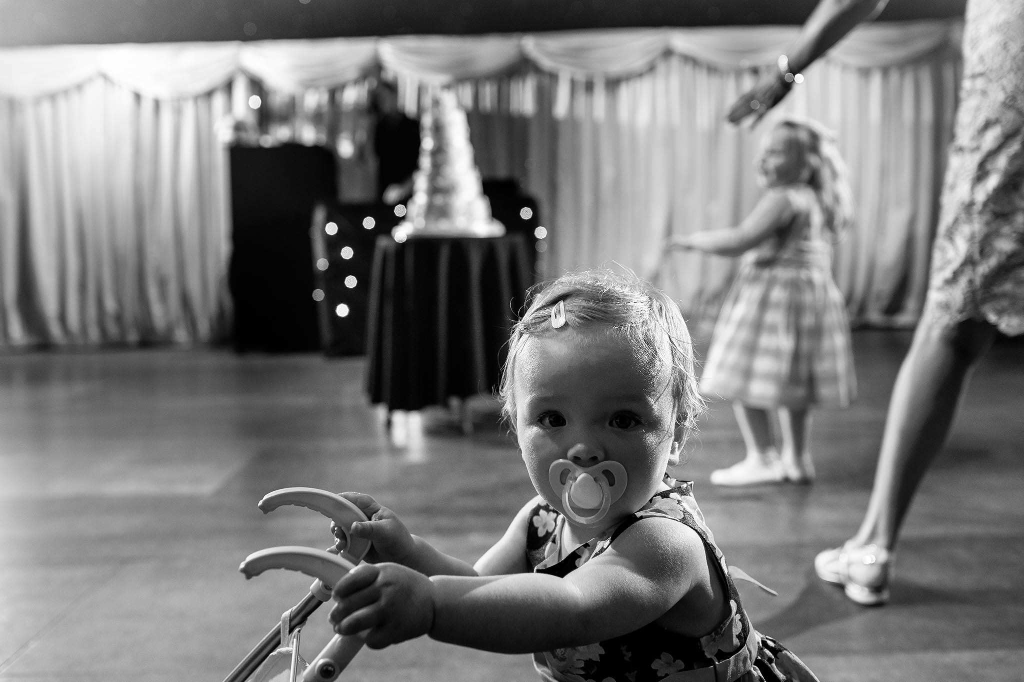 little girl walking in front of cake at wedding