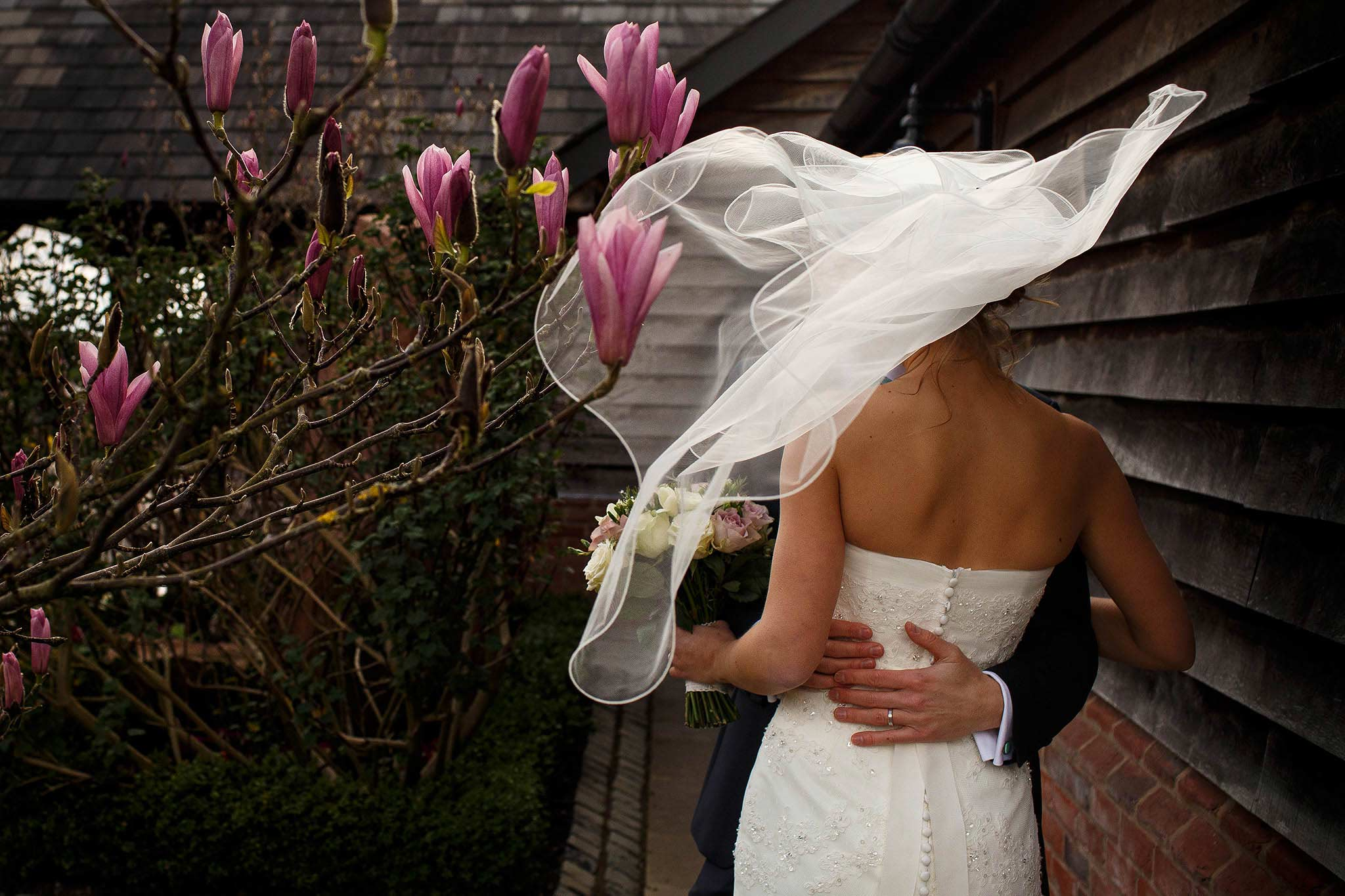 brides veil flowing into pink magnolia flowers at sandhole oak barn wedding