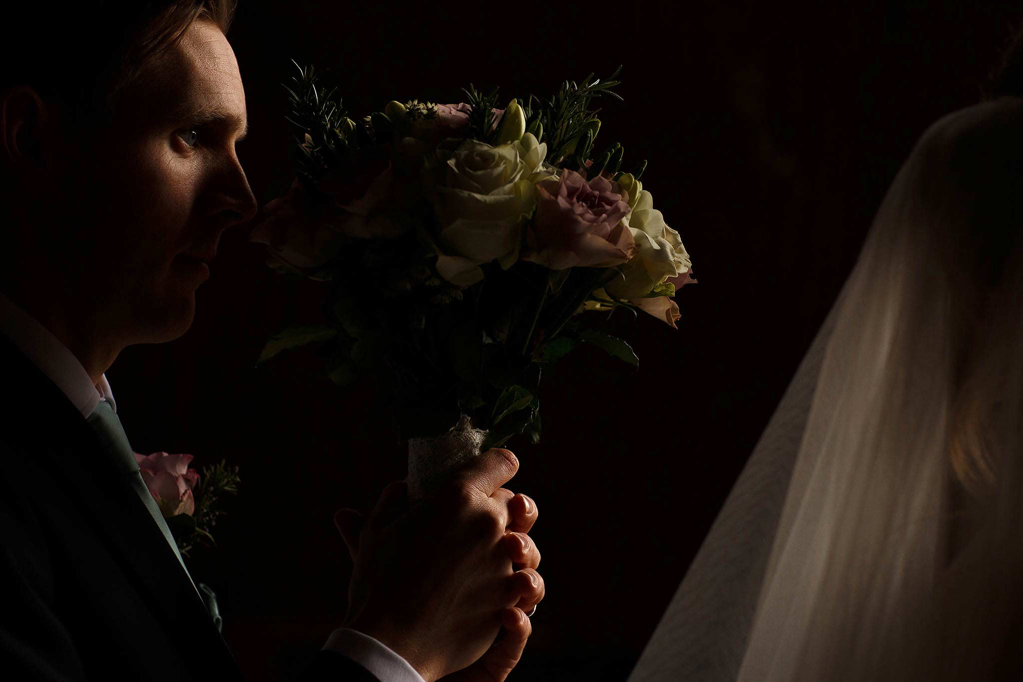 photograph of the groom with selective light on his face at sandhole oak barn wedding.