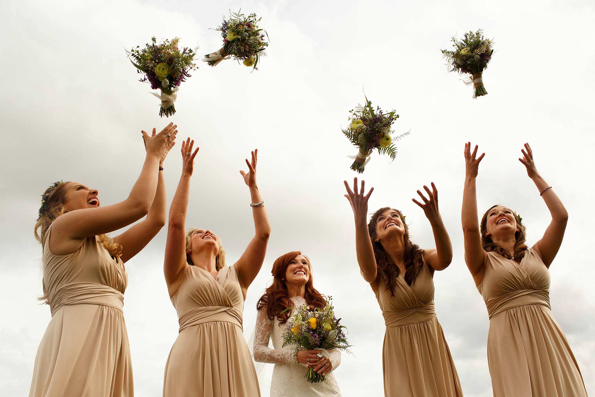 Bridesmaids all throwing their bouquets in the air at Sandhole Oak Barn wedding