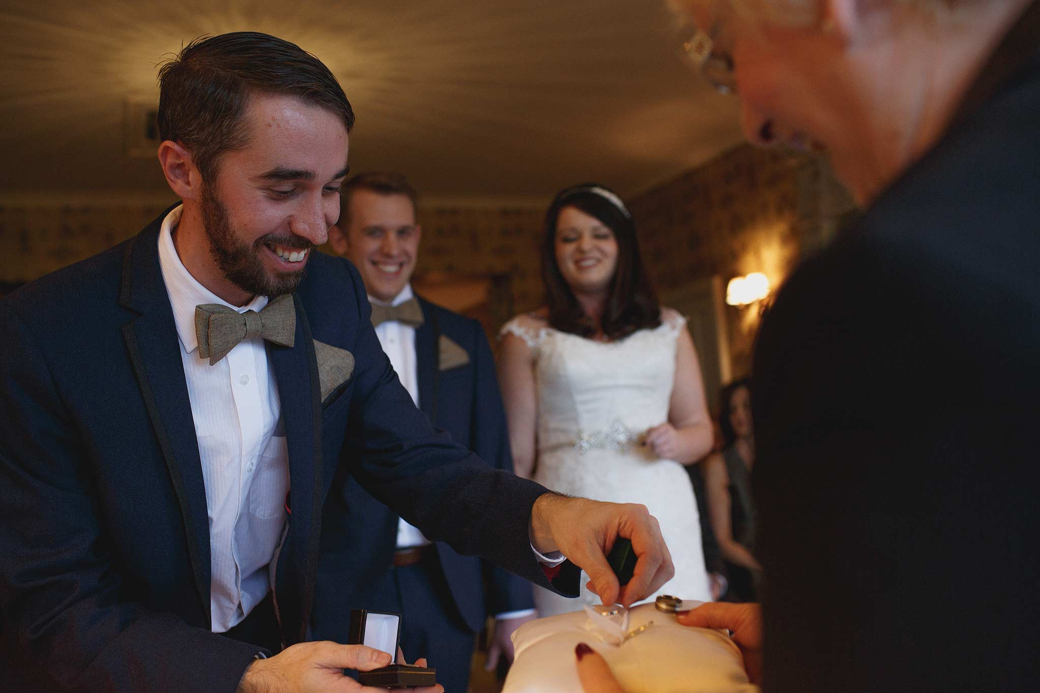 best man passing the rings to the registrar during wedding ceremony
