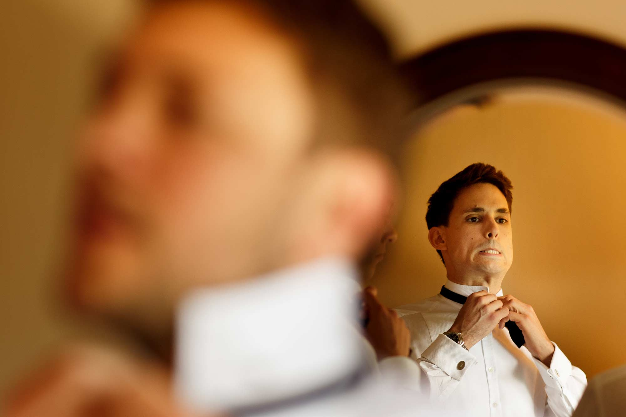 Groom struggling to fasten his bow tie facing a mirror