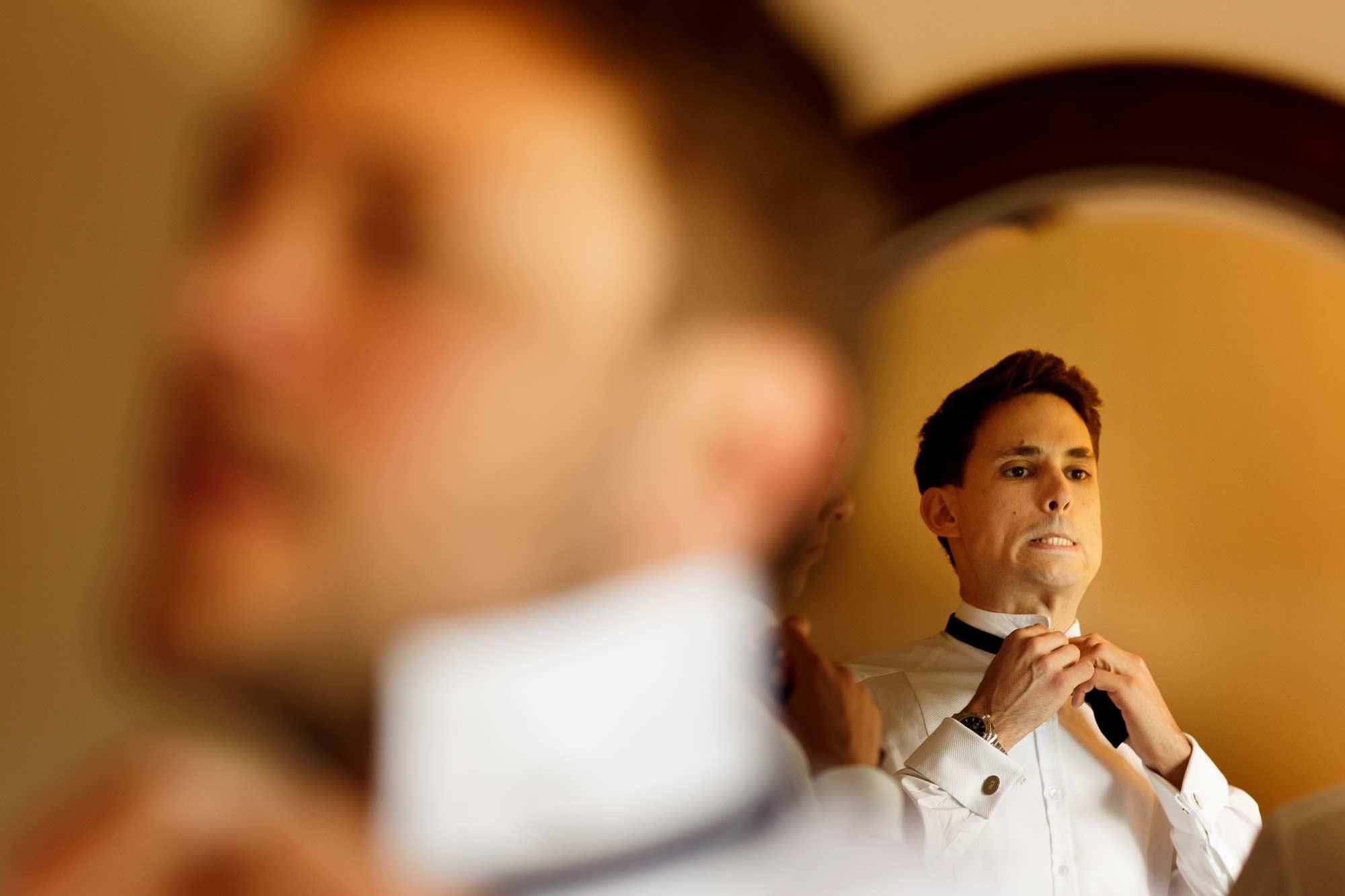 Groom struggling to fasten his bow tie facing a mirror