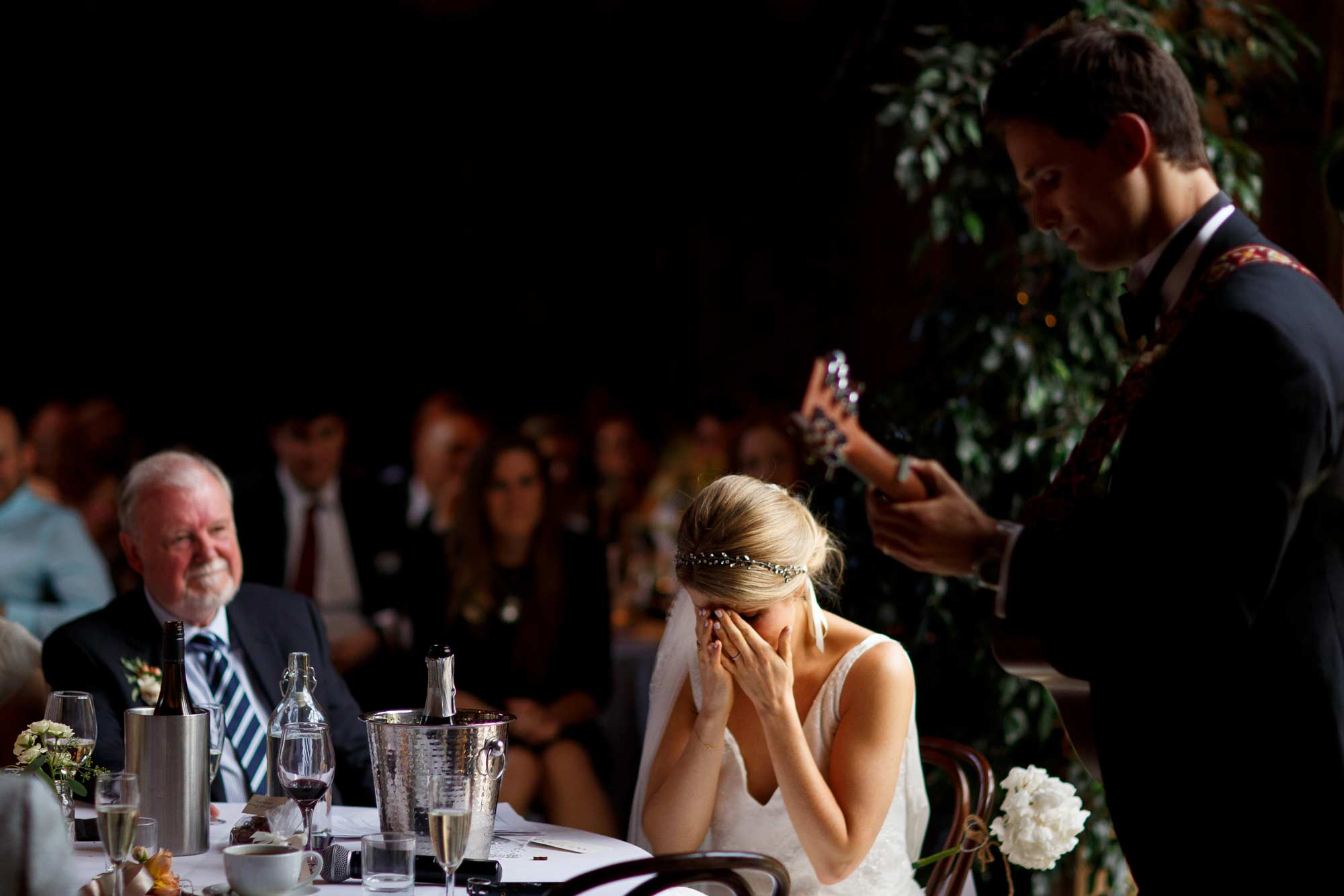 Emotional bride as her groom serenades her by playing the guitar during wedding speeches