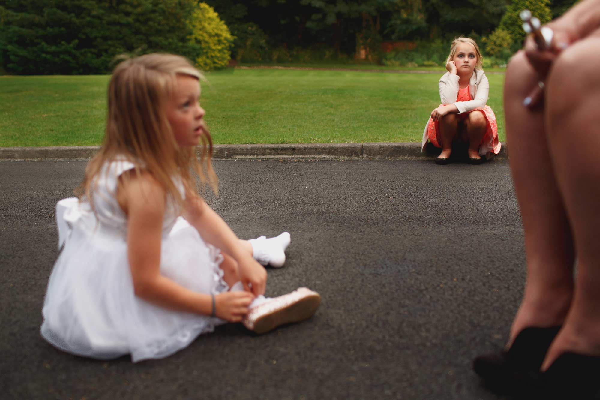 flower girls sulking sat on the floor outside at samlesbury hall wedding