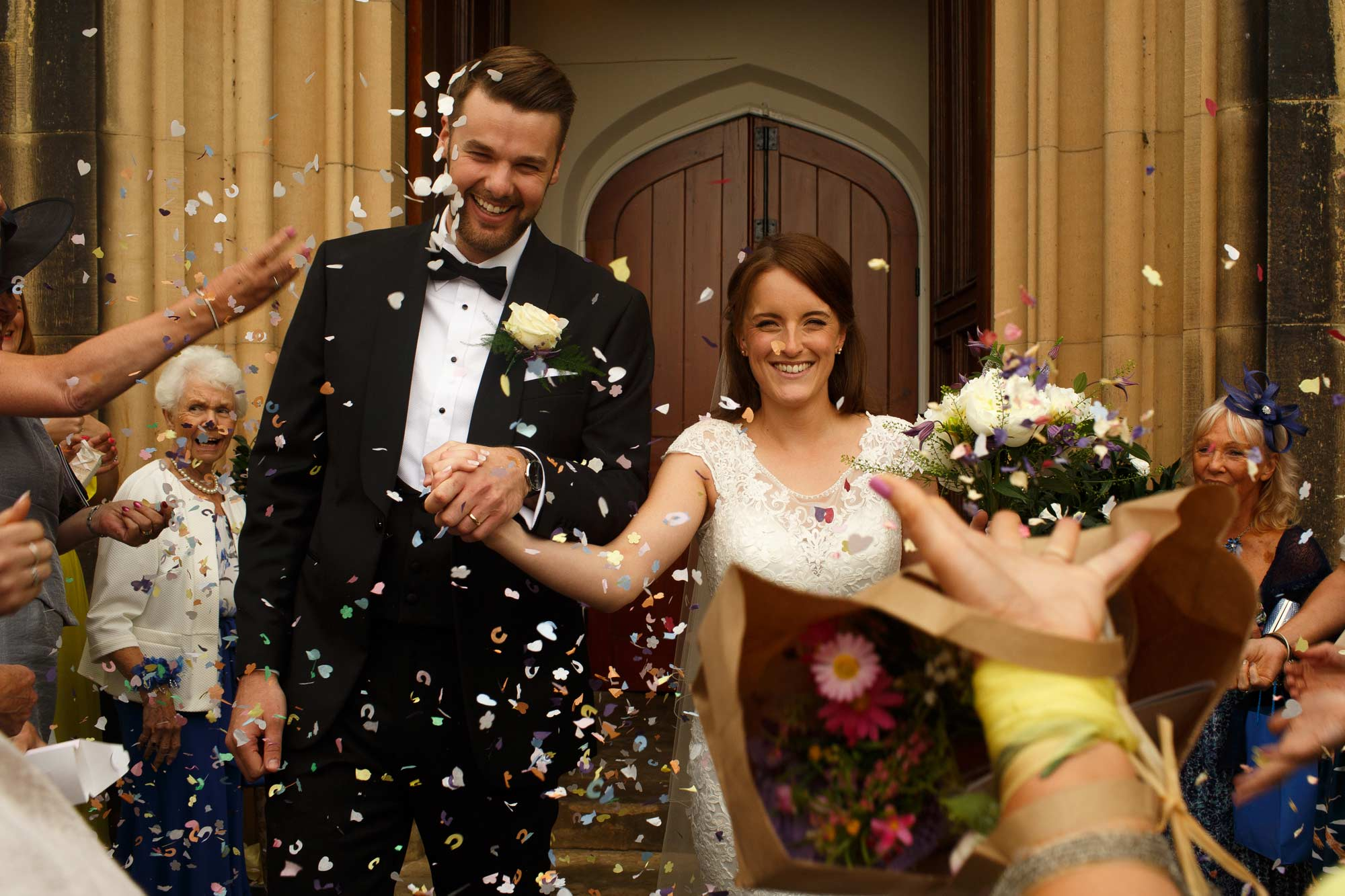 Confetti being throw over bride and groom at stonyhurst college wedding