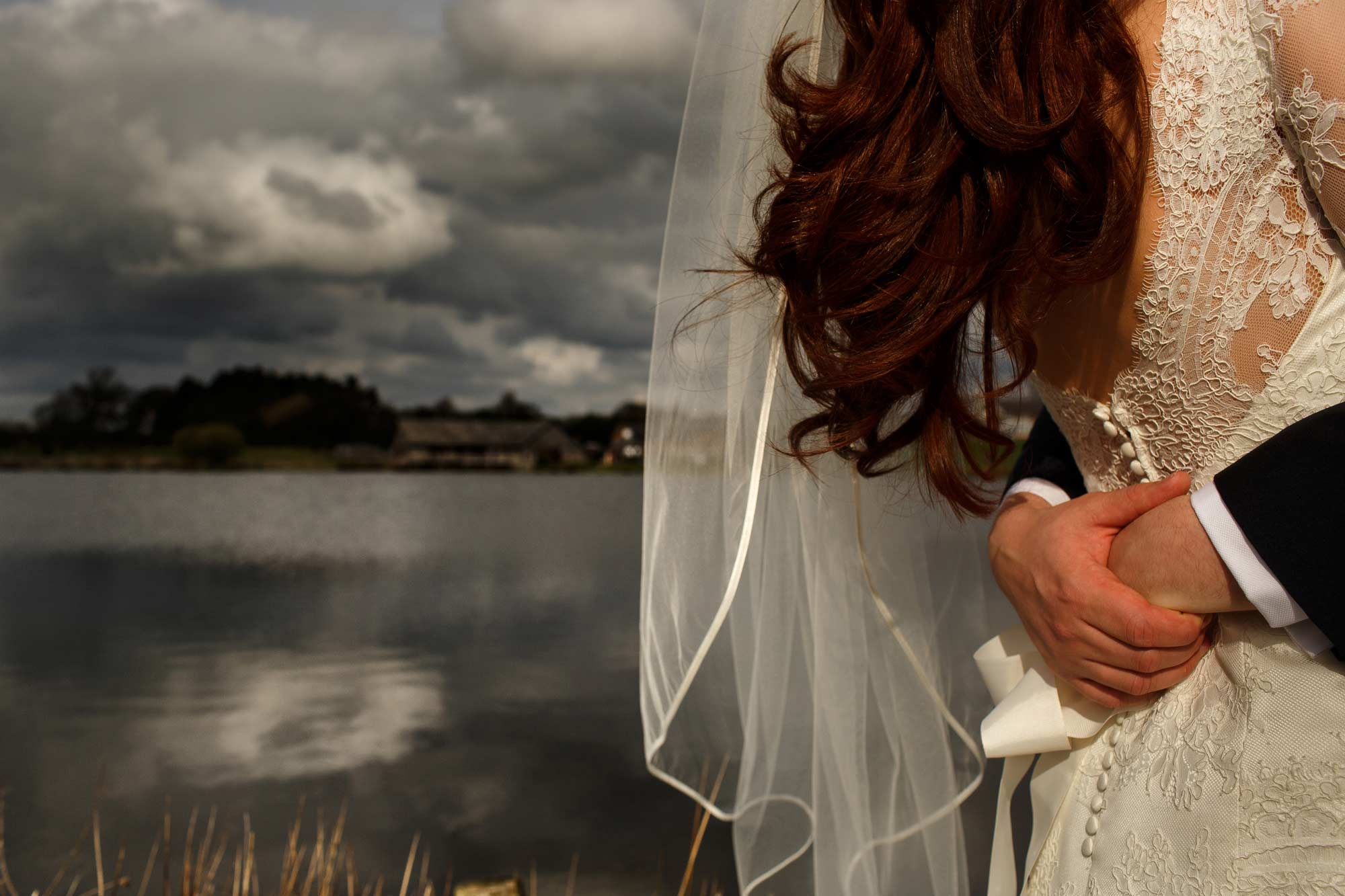 close up of brides wedding dress with the lake in the background at sandhole oak barn wedding