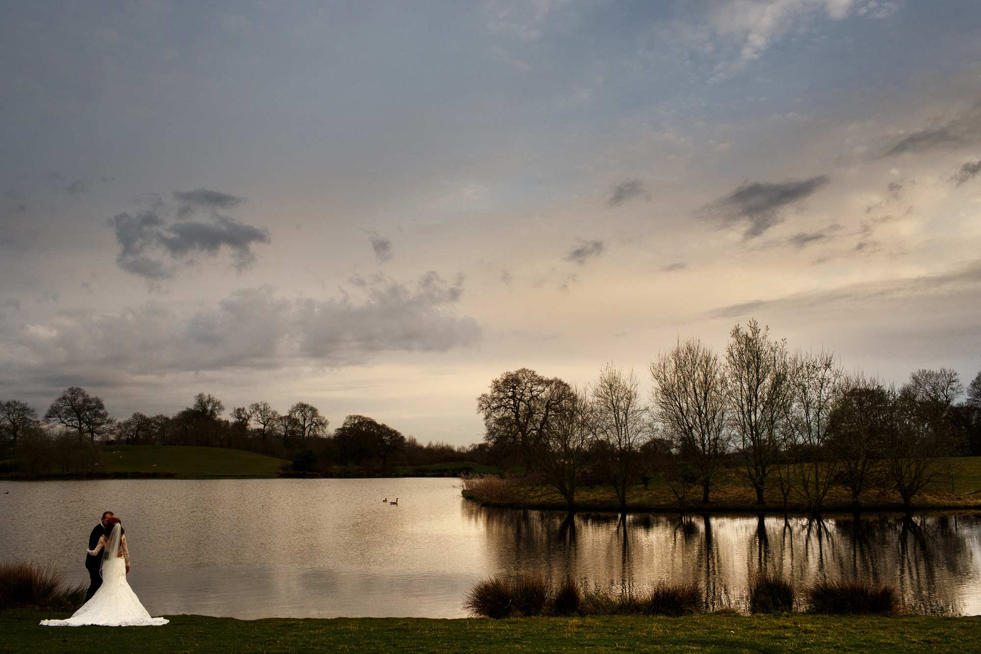 Landscape wedding photograph of lake at sandhole oak barn with the bride and groom on the edge of the lake