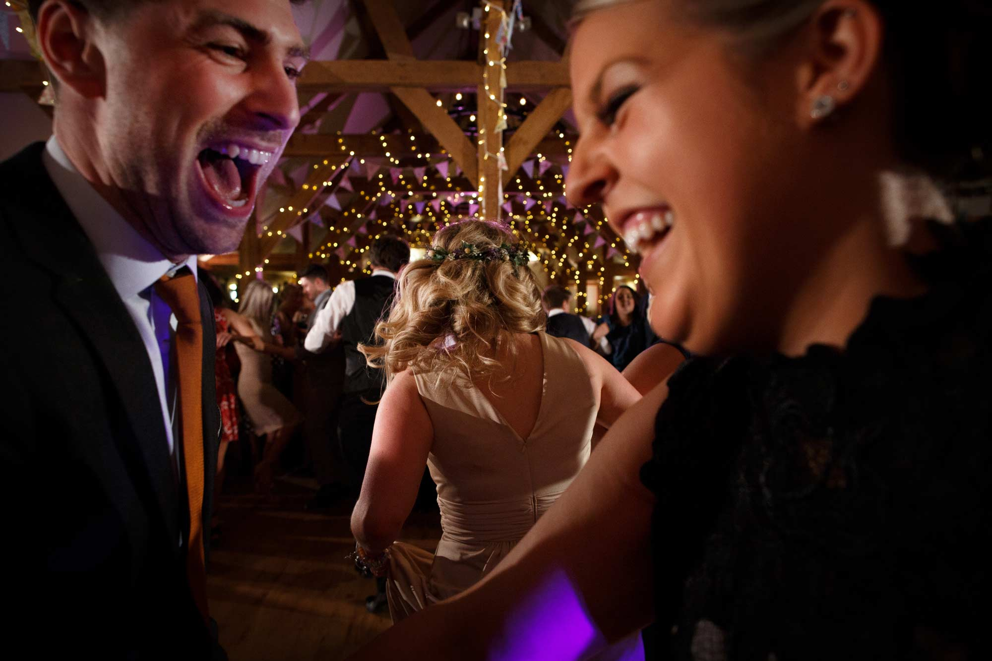 close up of guests laughing and dancing at sandhole oak barn wedding