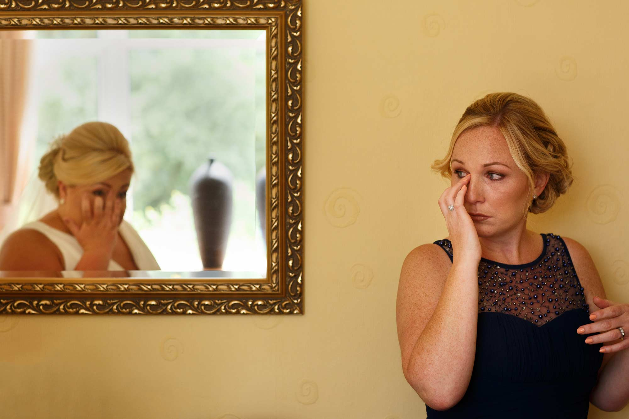 mirrored image of bride and bridesmaid wiping tears
