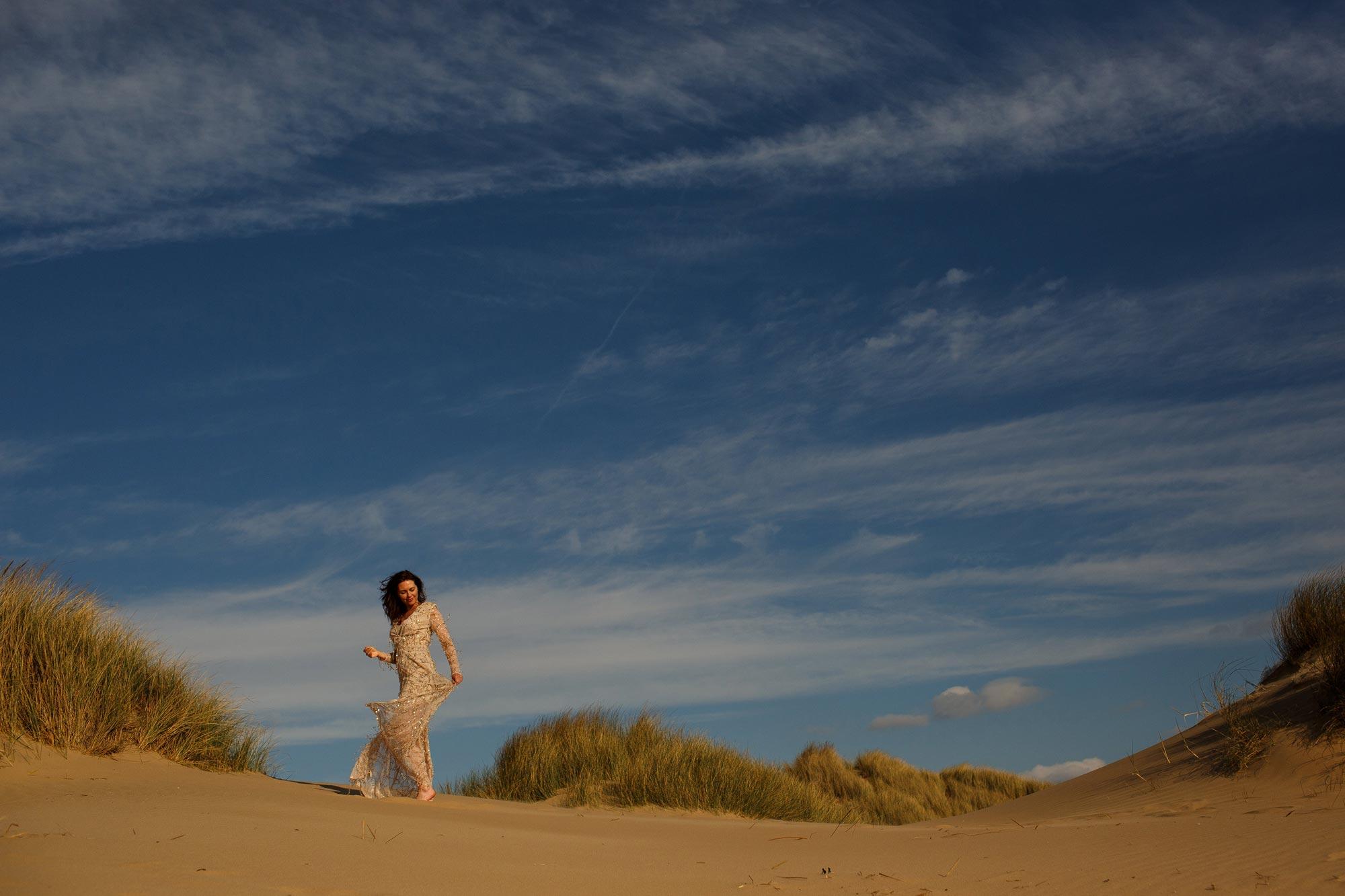 Bride walking across the sand dunes in gold sequin dress