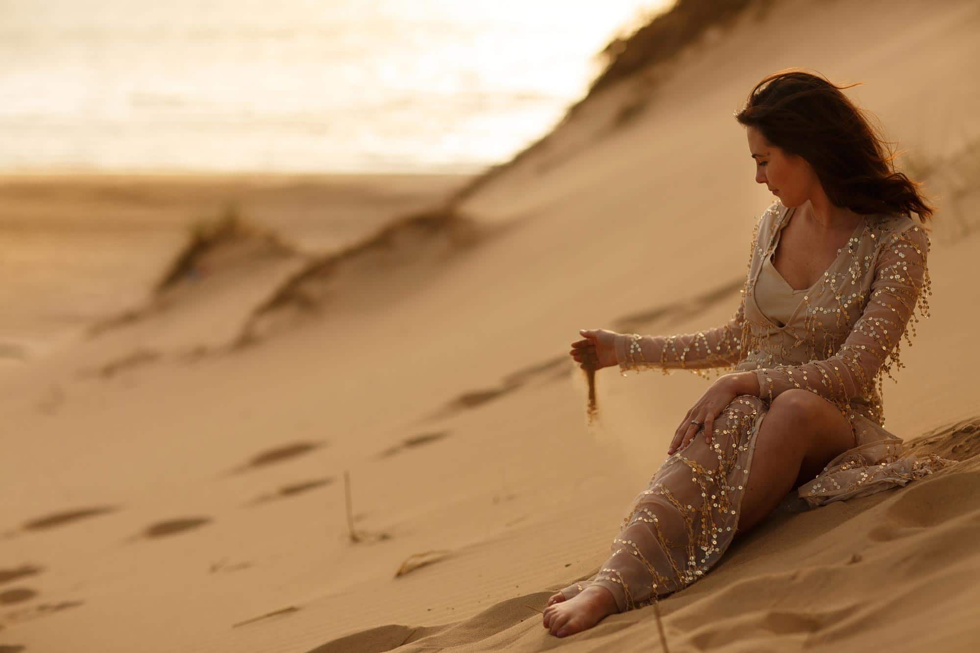 Bride sat on a beach playing with sand in sequin gold dress