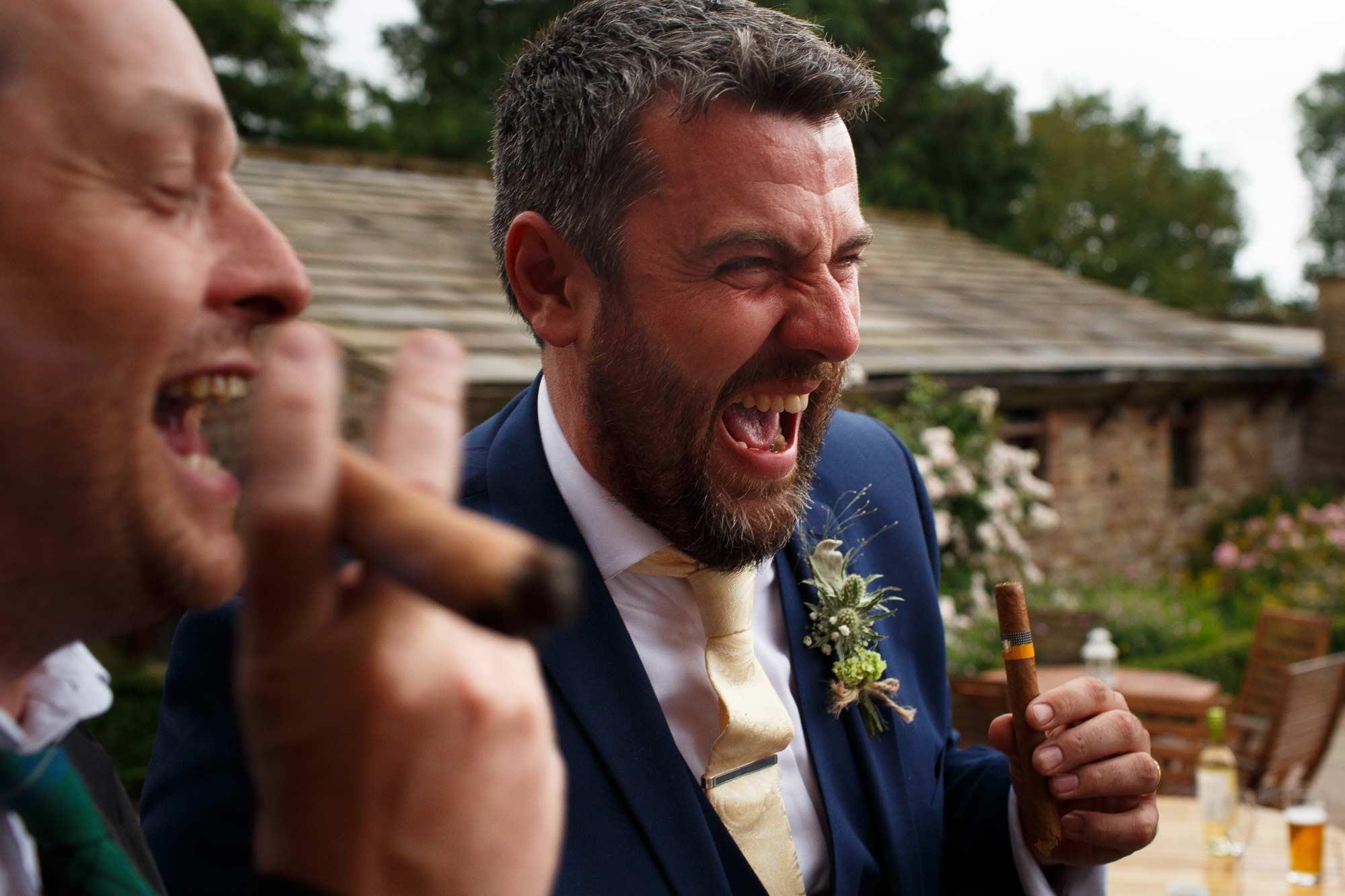 Groomsmen laughing smoking cigars at Browsholme Hall wedding