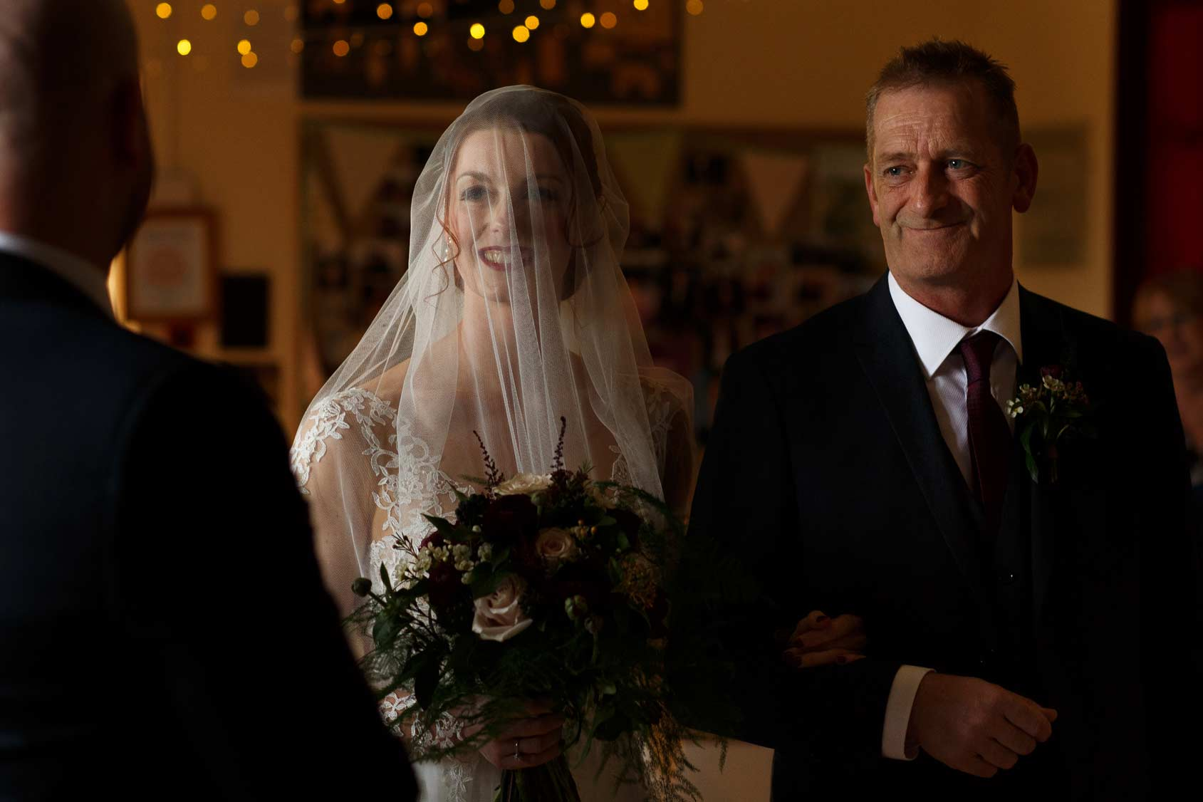 Bride with veil over the face as she walks down the aisle at Lancashire wedding