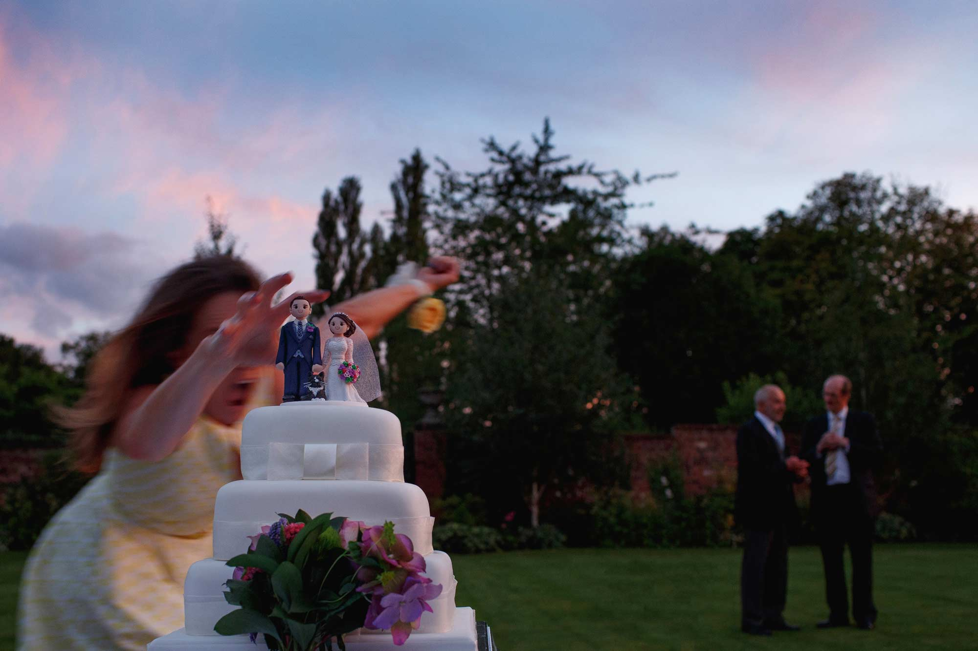 award wining wedding photograph of a wedding cake almost being knocked over