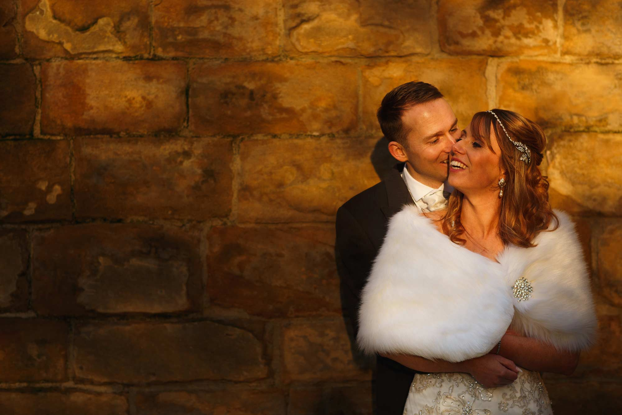 photograph of a bride and groom outside samlesbury hall in the winter sun