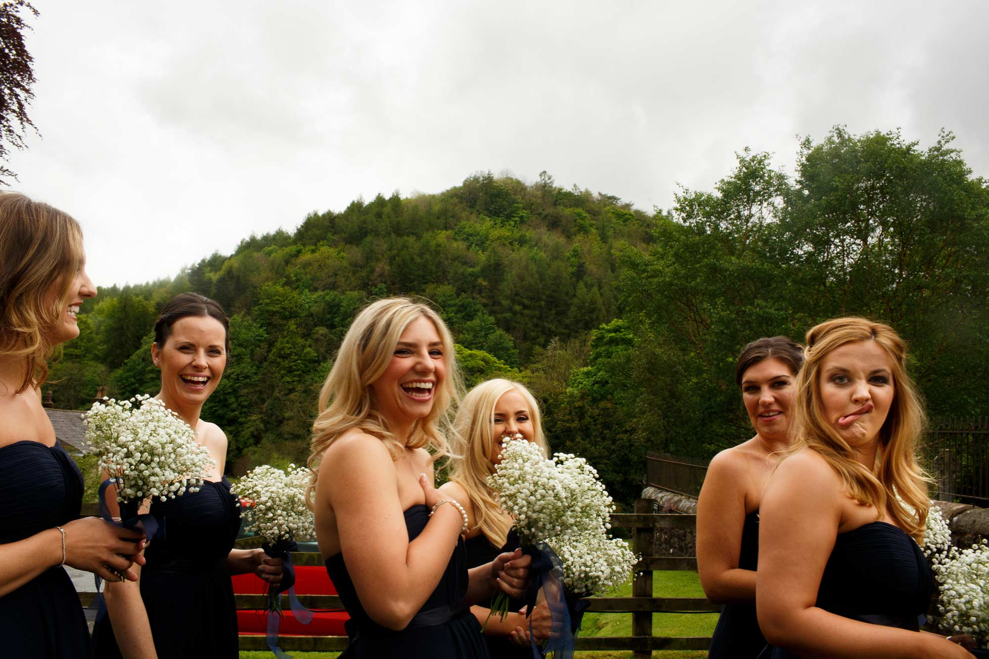 Bridesmaids laughing as they are in line about to enter the church at the inn at whitewell