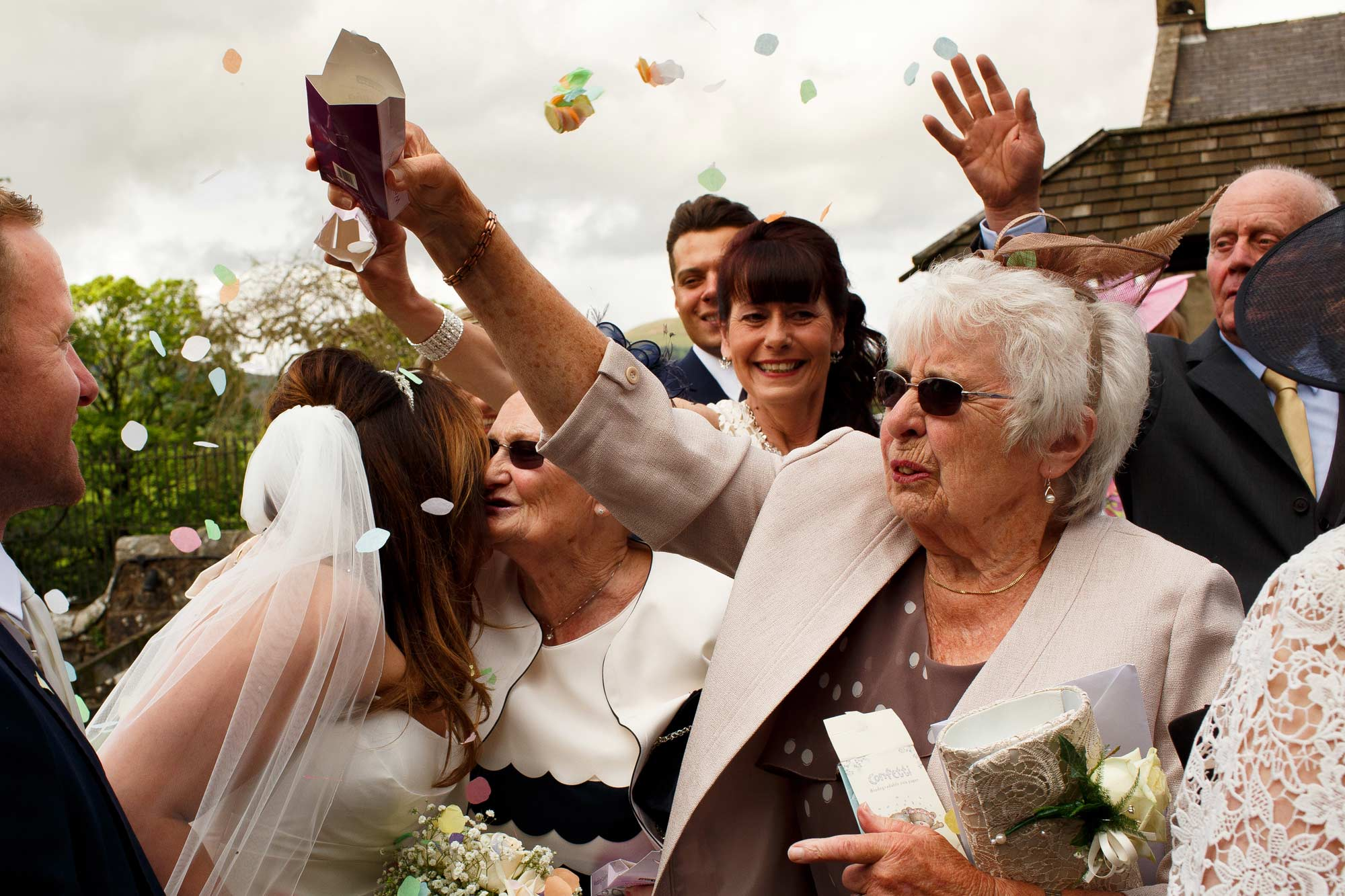 grans kissing bride and groom as guests throw confetti at inn at whitewell wedding